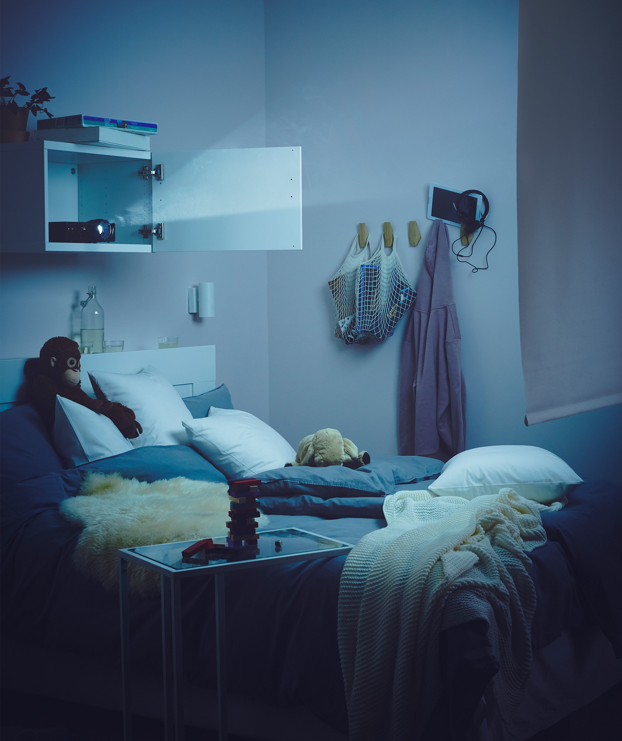 Bedroom dimly lit up by a projector in a wall cupboard above the bed, its beam aimed at a roller blind across the room.
