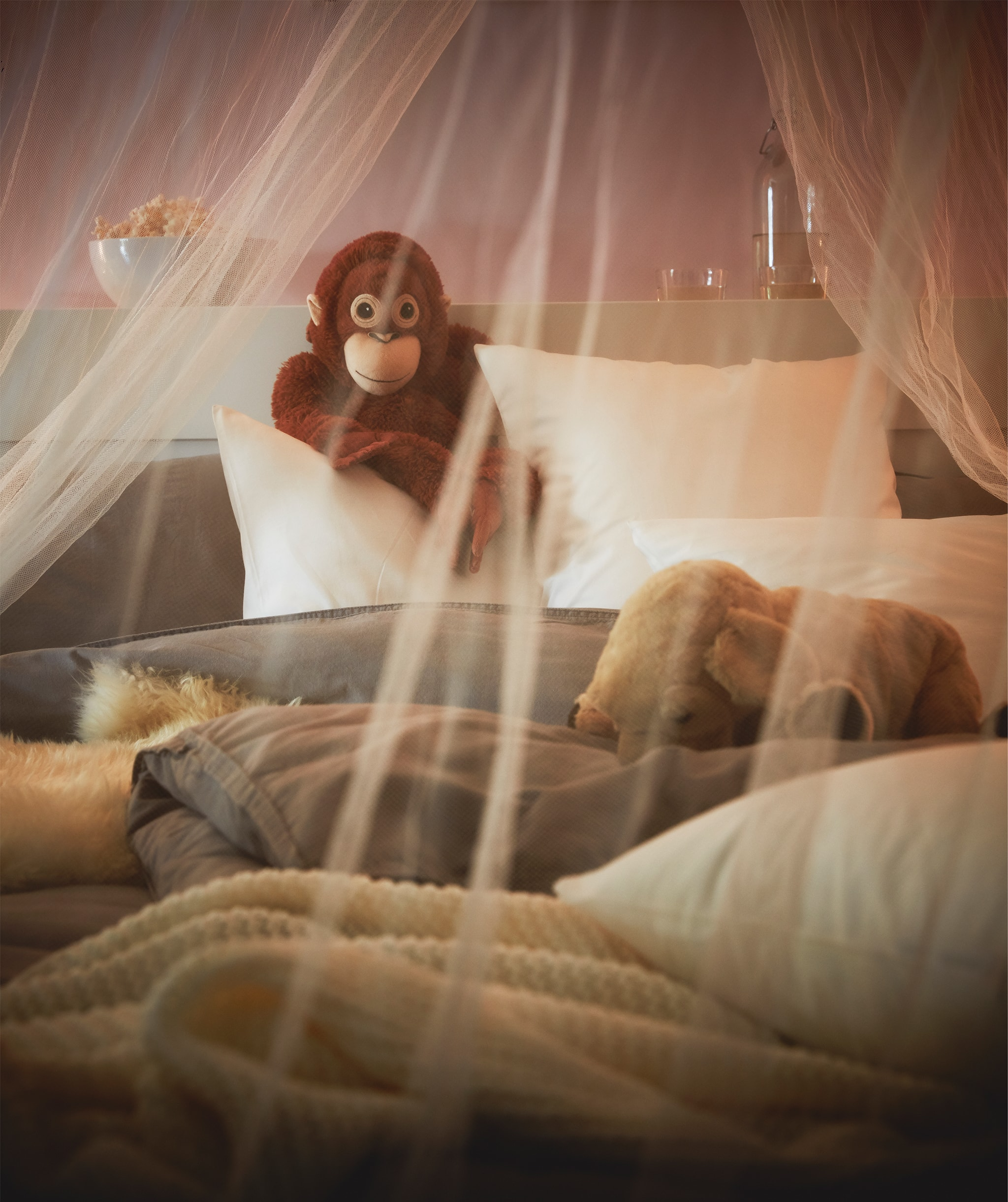 A mosquito net draped over a cosily lit, fluffy, unmade bed, a toy monkey propped up against the headboard.