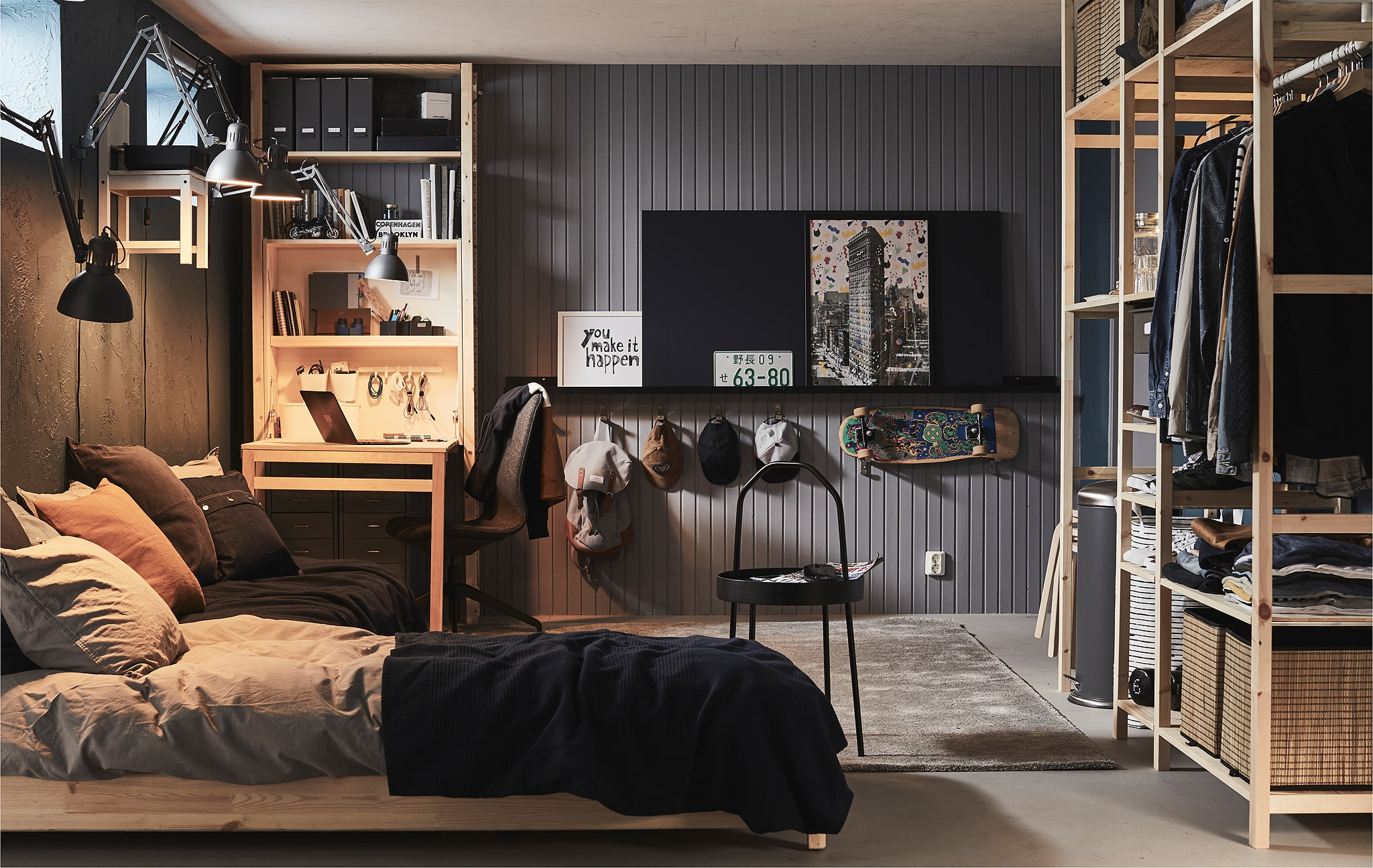Ruang berperabot lengkap dengan jendela tinggi, seperti berada di basement atau garasi, dengan tempat tidur, meja kerja dan berbagai ruang penyimpanan.