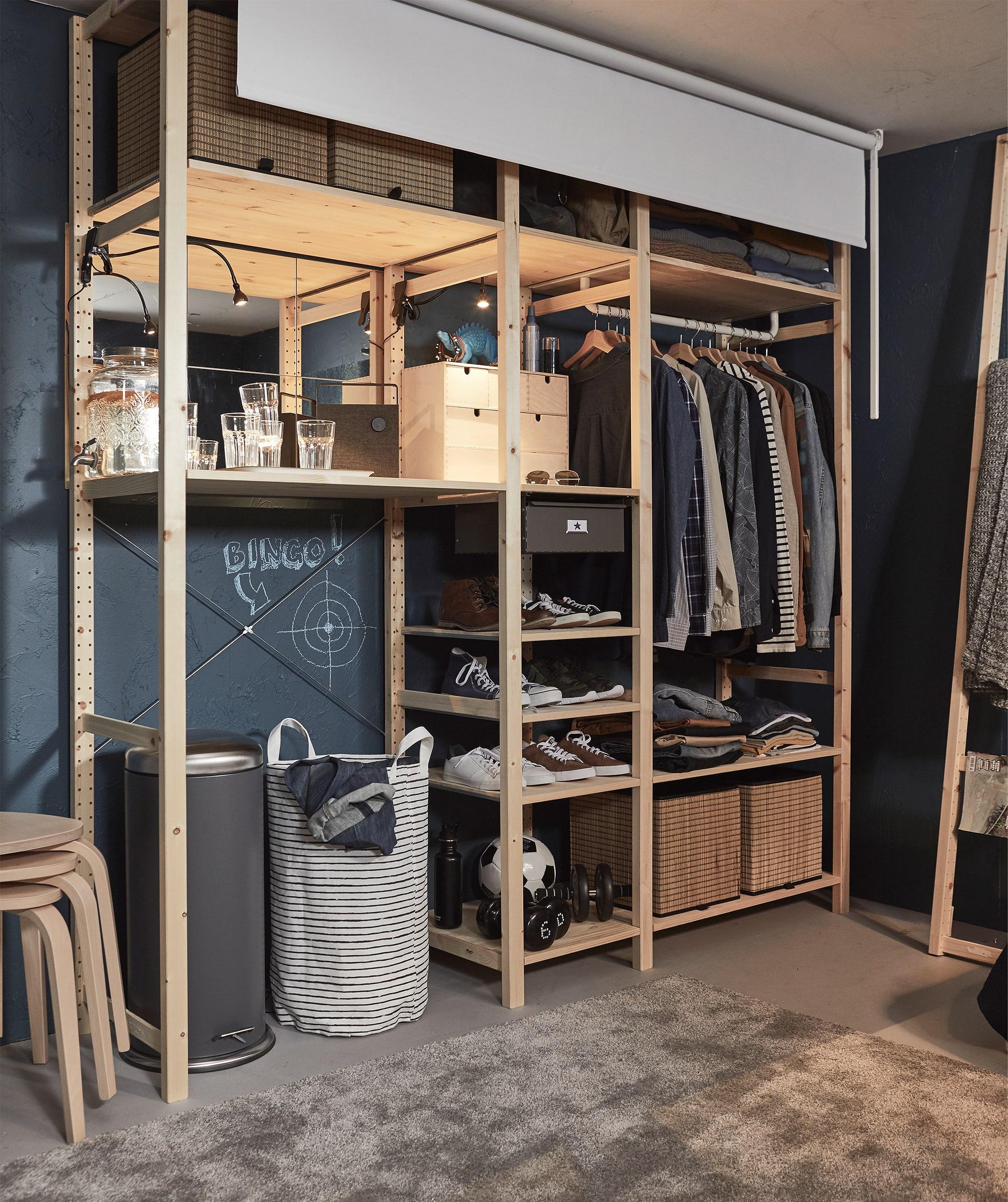 Sudut ruangan dengan unit rak besar berisi pakaian; sebuah tirai gulung yang dapat di tarik ke bawah ada di depannya.