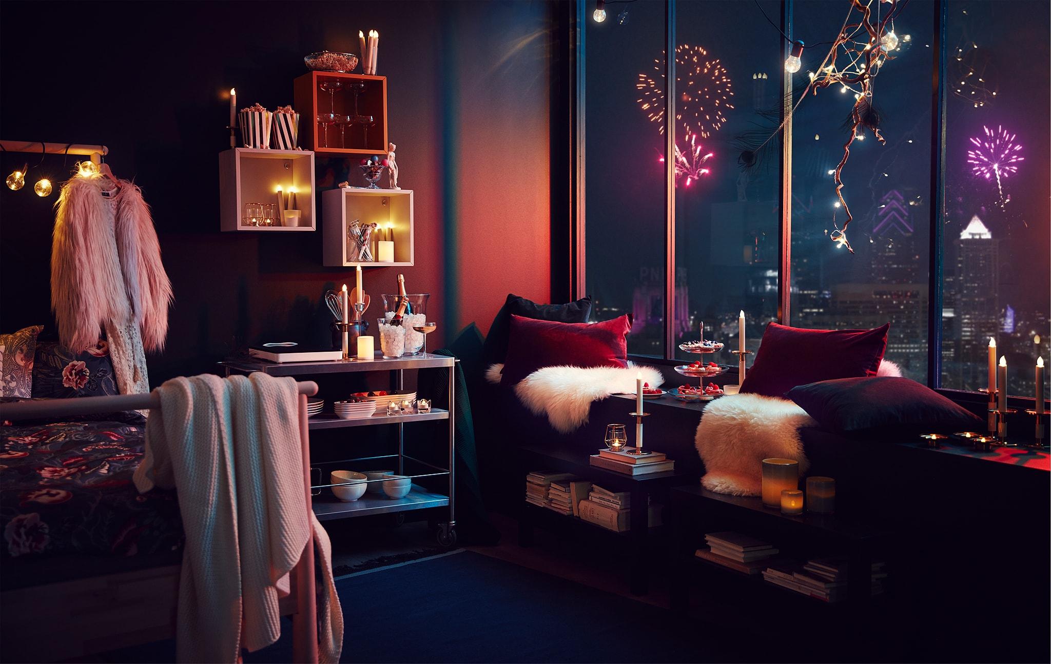 Interior apartemen dengan dekorasi pesta dan lampu; kembang api dari kota terlihat melalui jendela tinggi.