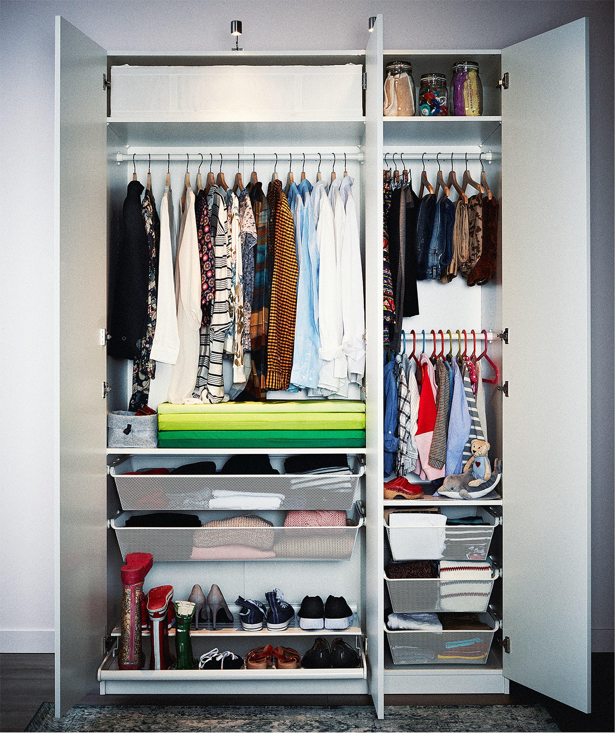 Gabungan lemari dua pintu dan satu pintu dengan koleksi pakaian yang sangat tertata pada gantungan dan rak, di laci dan kotak.