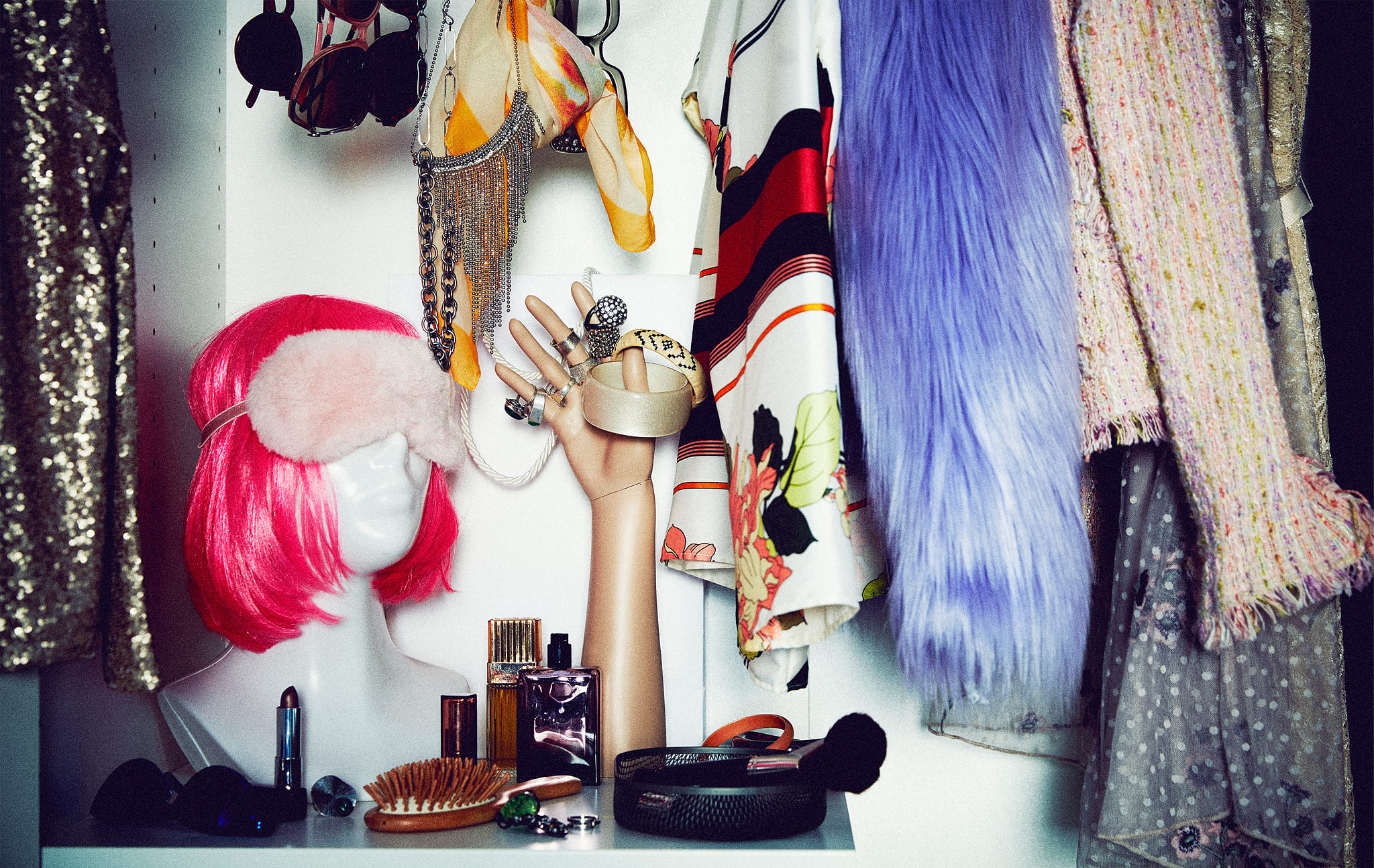 Bagian lemari yang berisi pakaian dan aksesoris pesta; patung dengan wig warna neon, maneken tangan dengan cincin.
