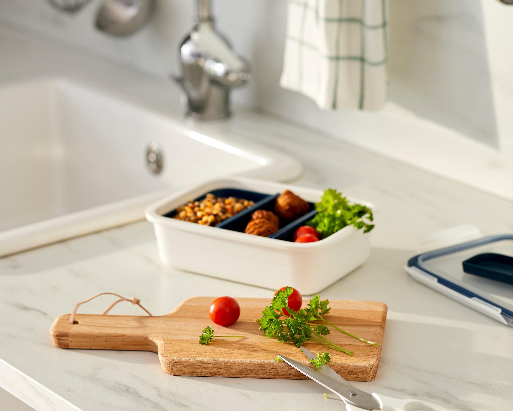 Meja dapur dengan makanan di sebuah wadah berkompartemen, talenan dengan tomat dan rempah-rempah yang baru dipotong.
