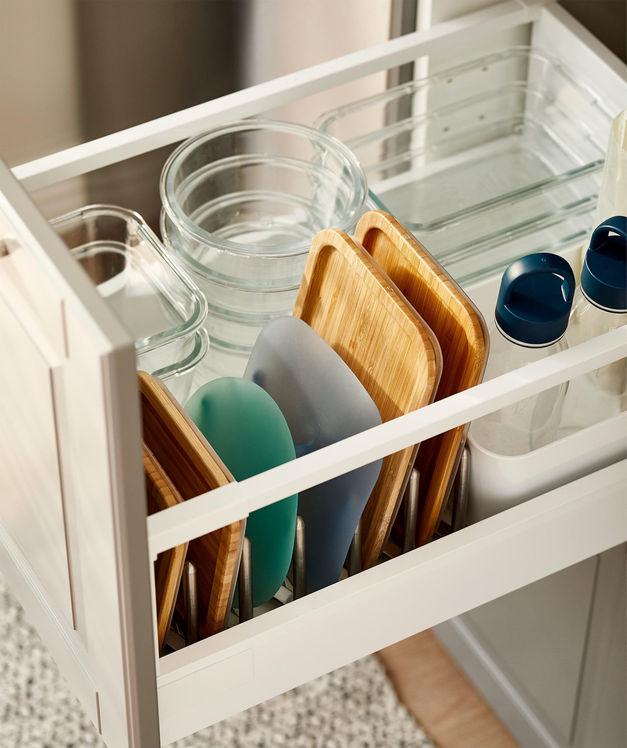 Laci dapur penuh dengan tumpukan wadah kaca dalam berbagai ukuran, masing-masing tutup disimpan di pengaturan tutup panci.