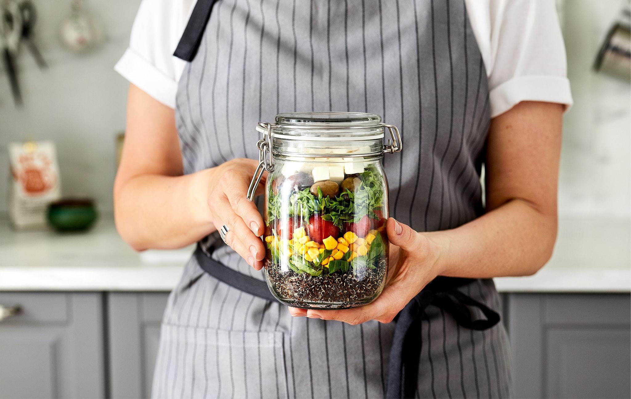 Wanita dengan celemek berdiri di dapur, kedua tangannya memegang toples kaca berisi salad berlapis-lapis yang berwarna-warni.