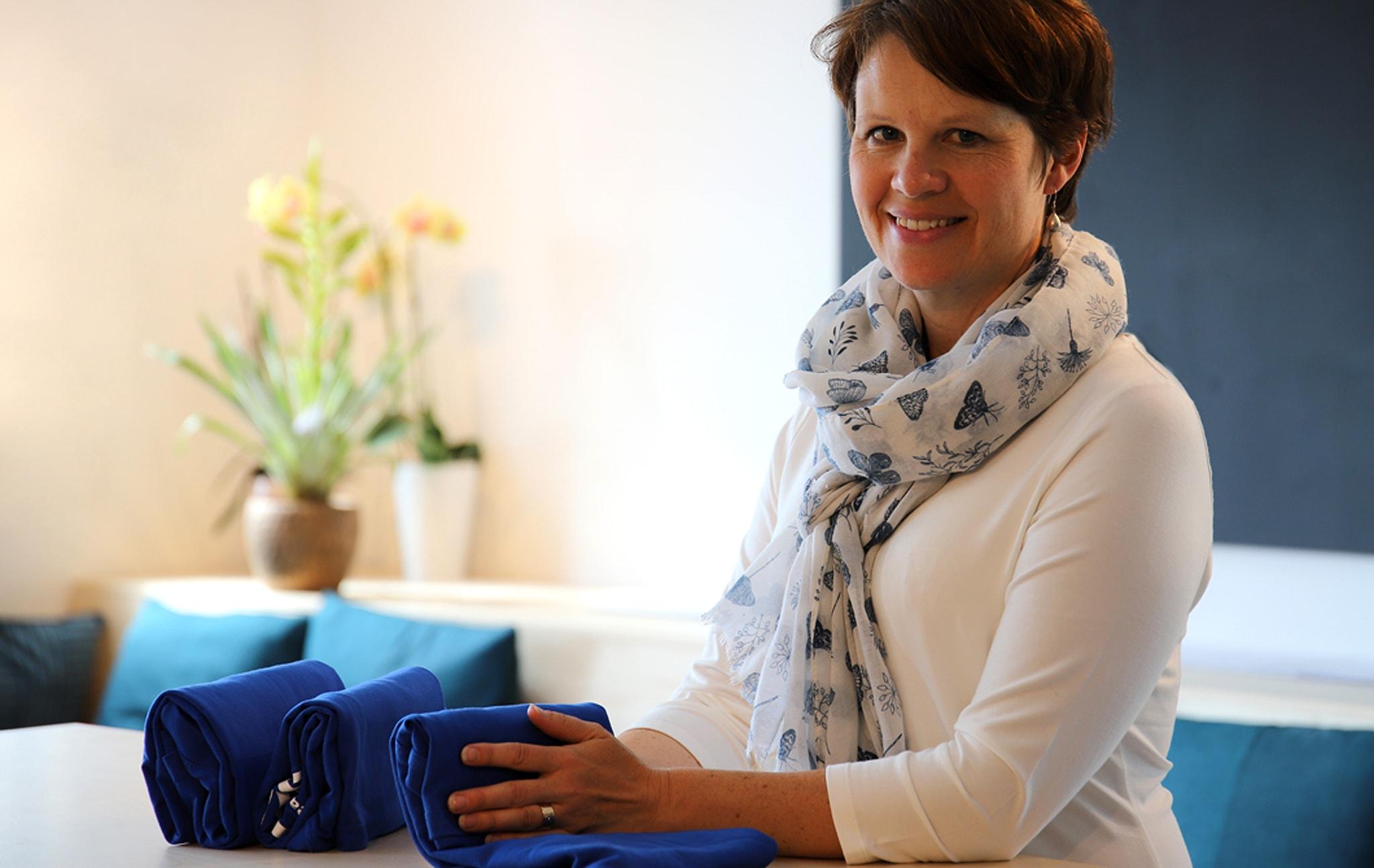 Wanita duduk dekat meja sambil tersenyum ke arah kamera, sambil melipat tekstil.