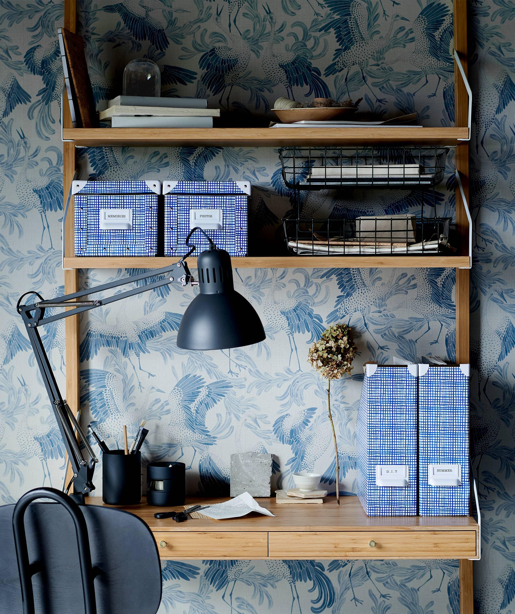Rak yang dipasang di dinding merangkap sebagai ruang kerja kecil; berbagai penyimpanan, lampu meja, kursi kantor, wallpaper bermotif grafis.