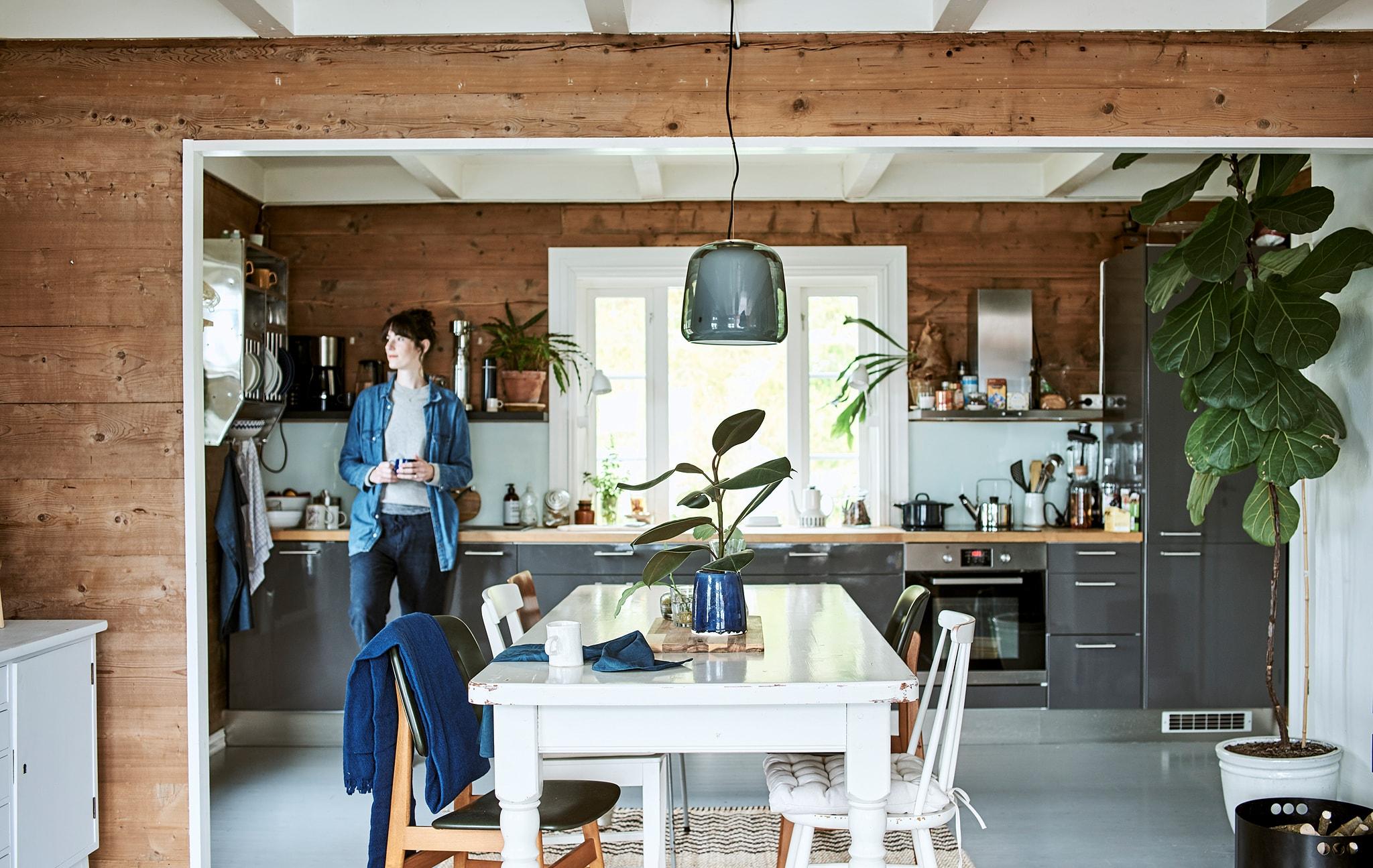 Seorang wanita bersandar pada kabinet abu-abu mengilap di dapur terbuka yang menyatu dengan ruang makan, terdapat meja dan kursi kayu putih.
