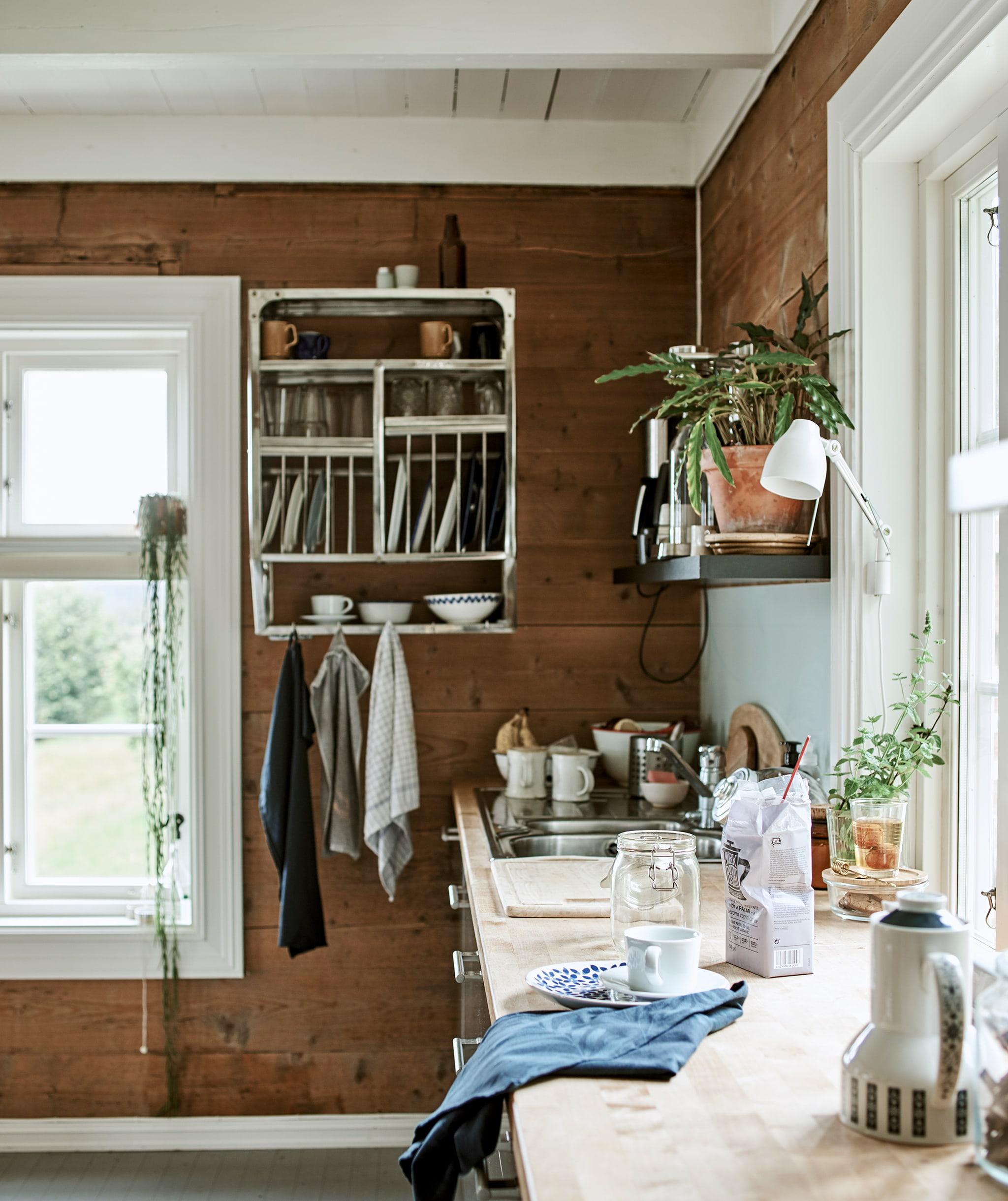 Meja dapur berpanel kayu dengan penyimpanan terbuka serta kabinet dinding bertema industri berisi barang pecah belah.