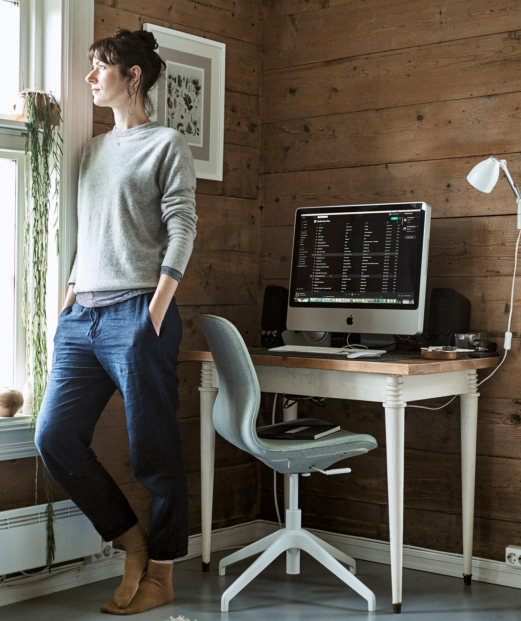 Seorang wanita melihat keluar jendela di sudut ruangan yang telah disulap menjadi ruang kerja dengan meja dan kursi putar.