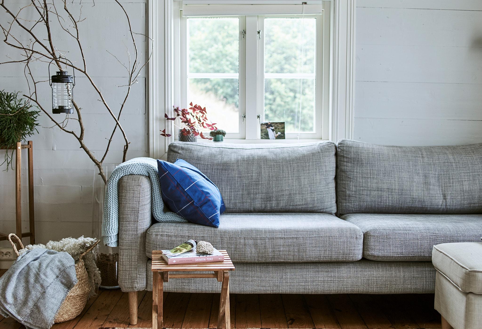 Sebuah sofa abu-abu di depan jendela, selimut wol yang disimpan di keranjang dan cabang-cabang pohon mencuat dari dalam vas kaca besar.