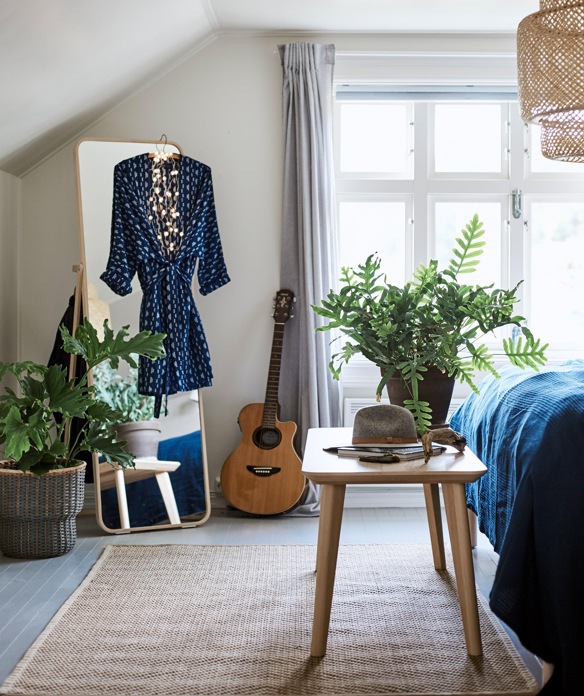 Kamar tidur dengan lampu plafon dan karpet, cermin dengan gaun yang tergantung di atasnya serta bangku di ujung tempat tidur.