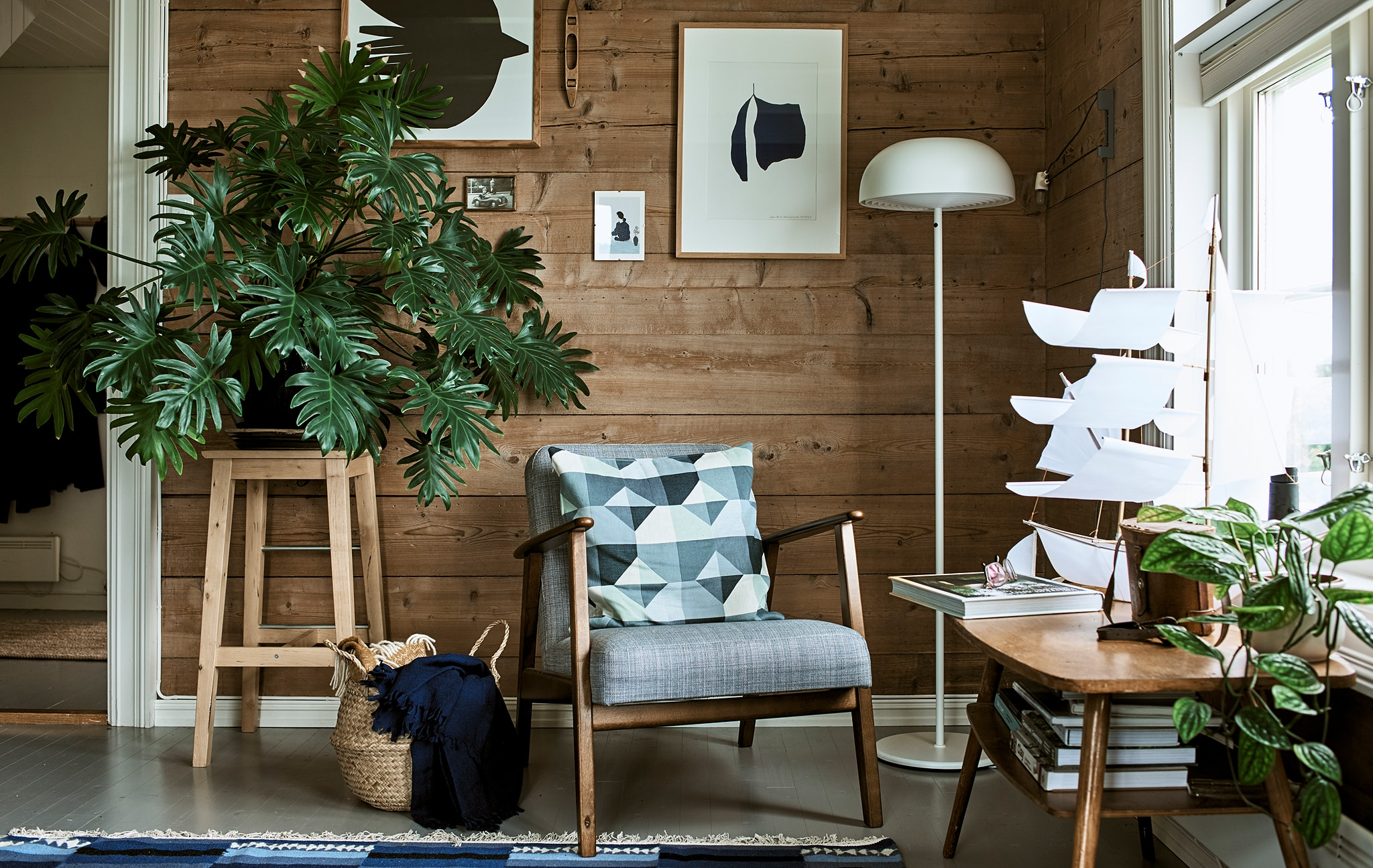 Ruang keluarga bertema rustic dengan kursi kayu berlengan, lampu lantai putih dan bangku yang digunakan sebagai stand tanaman untuk tumbuhan berdaun lebar.