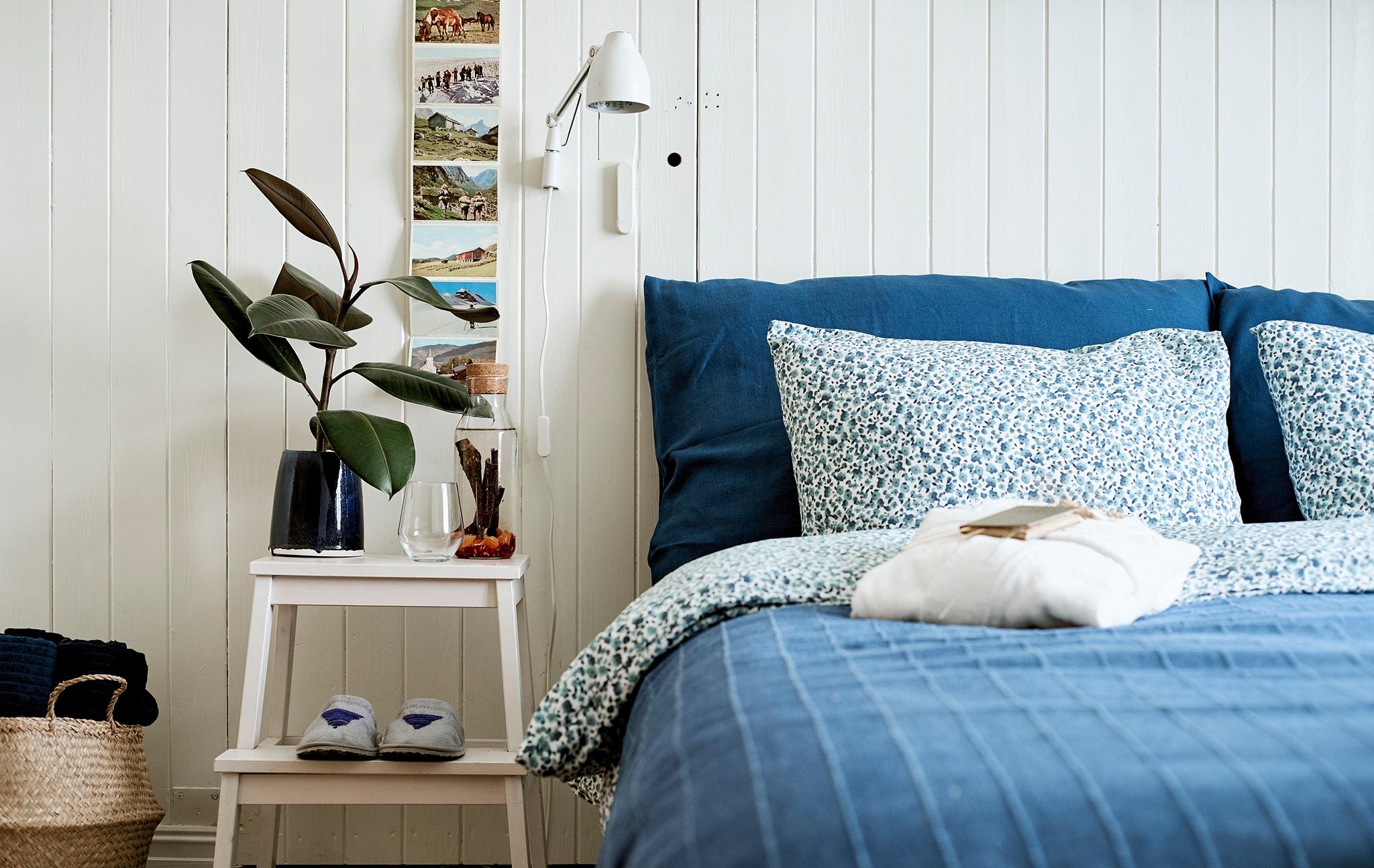 Sebuah tempat tidur dengan seprei berwarna biru, bangku tangga yang berfungsi ganda menjadi meja samping, di atasnya terdapat botol air infus dan gelas minum.
