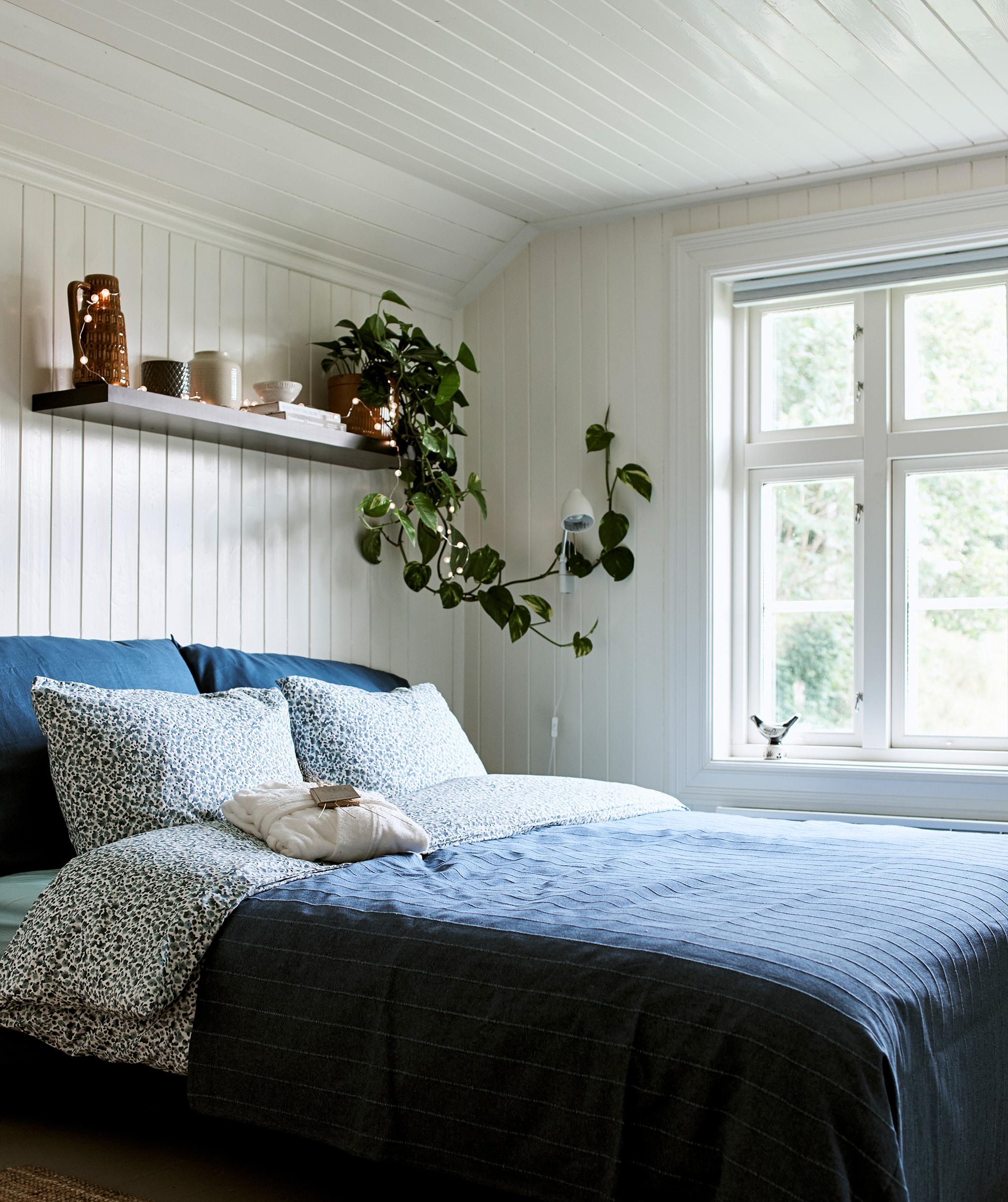 Kamar tidur dengan gaya rumah pertanian yang memiliki panel kayu putih dan tempat tidur dengan seprai biru dengan rak dinding di bagian atas untuk menyimpan dan memajang.