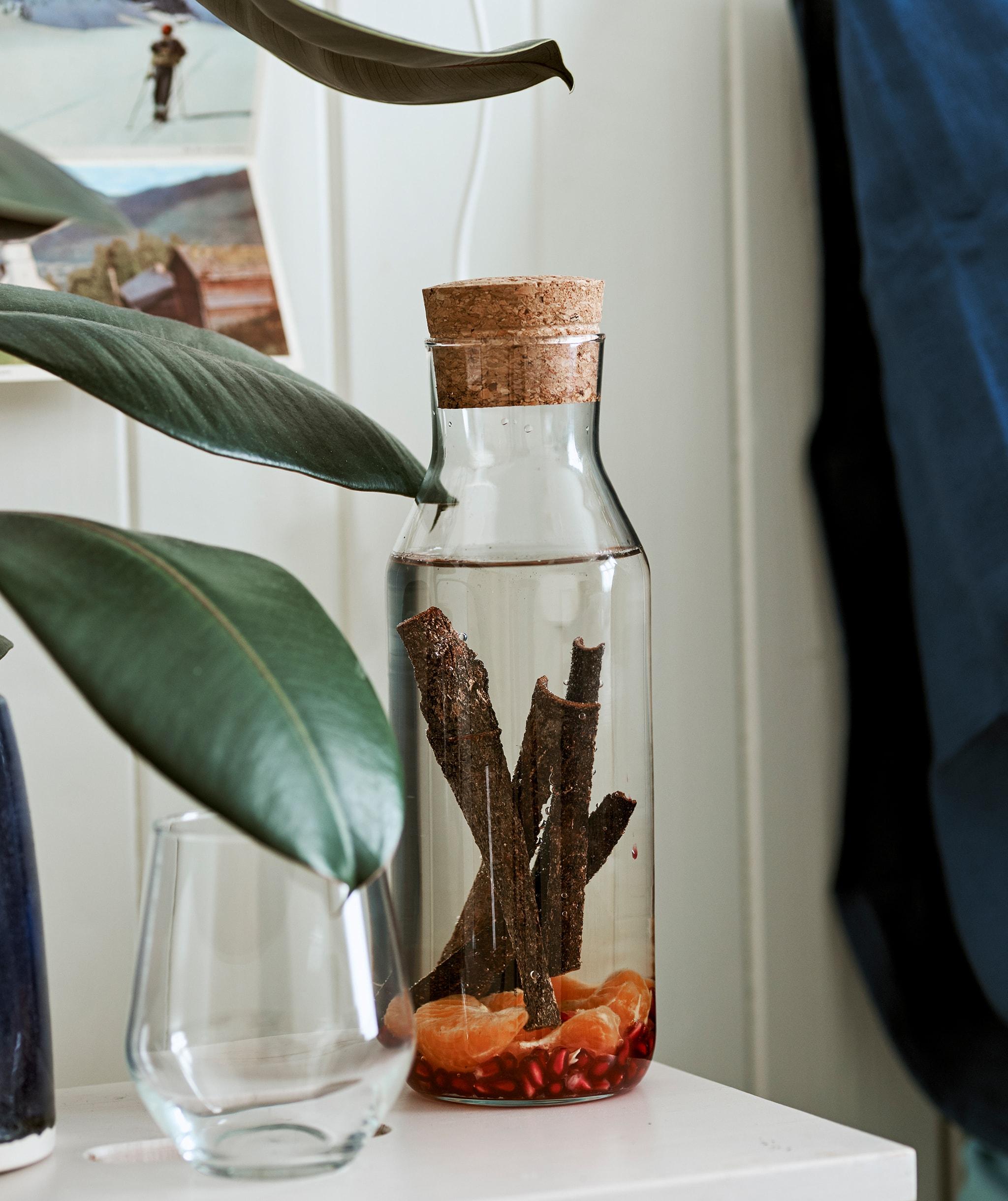 Satu gelas karafe dengan sumbat gabus diisi dengan air yang berisi batang kayu manis dan buah, di samping sebuah gelas minum.