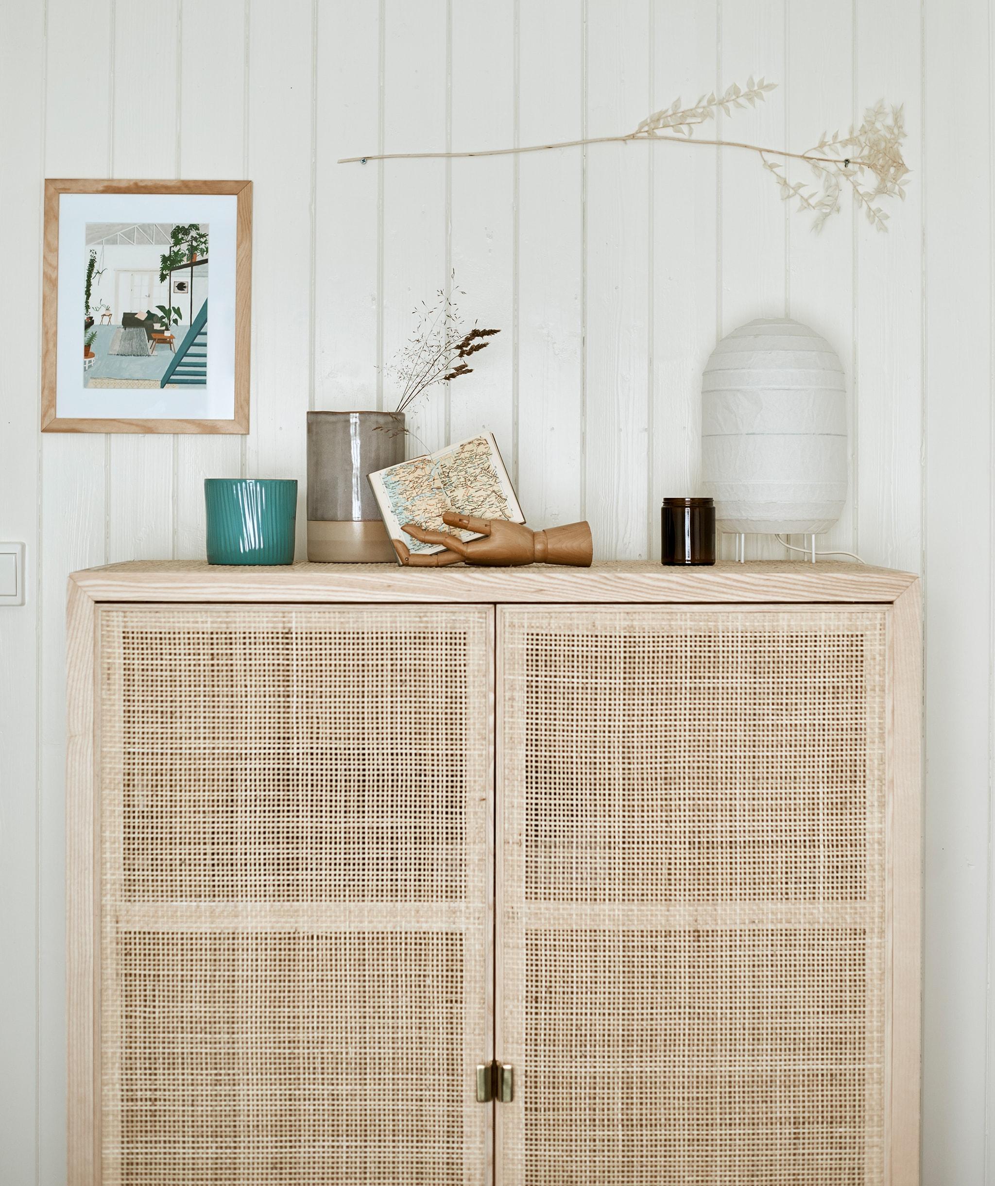 Lemari penyimpanan berbahan kayu yang tinggi dengan pintu anyaman dipasang pada dinding berpanel dengan lentera kertas dan benda-benda yang dipajang di atasnya.