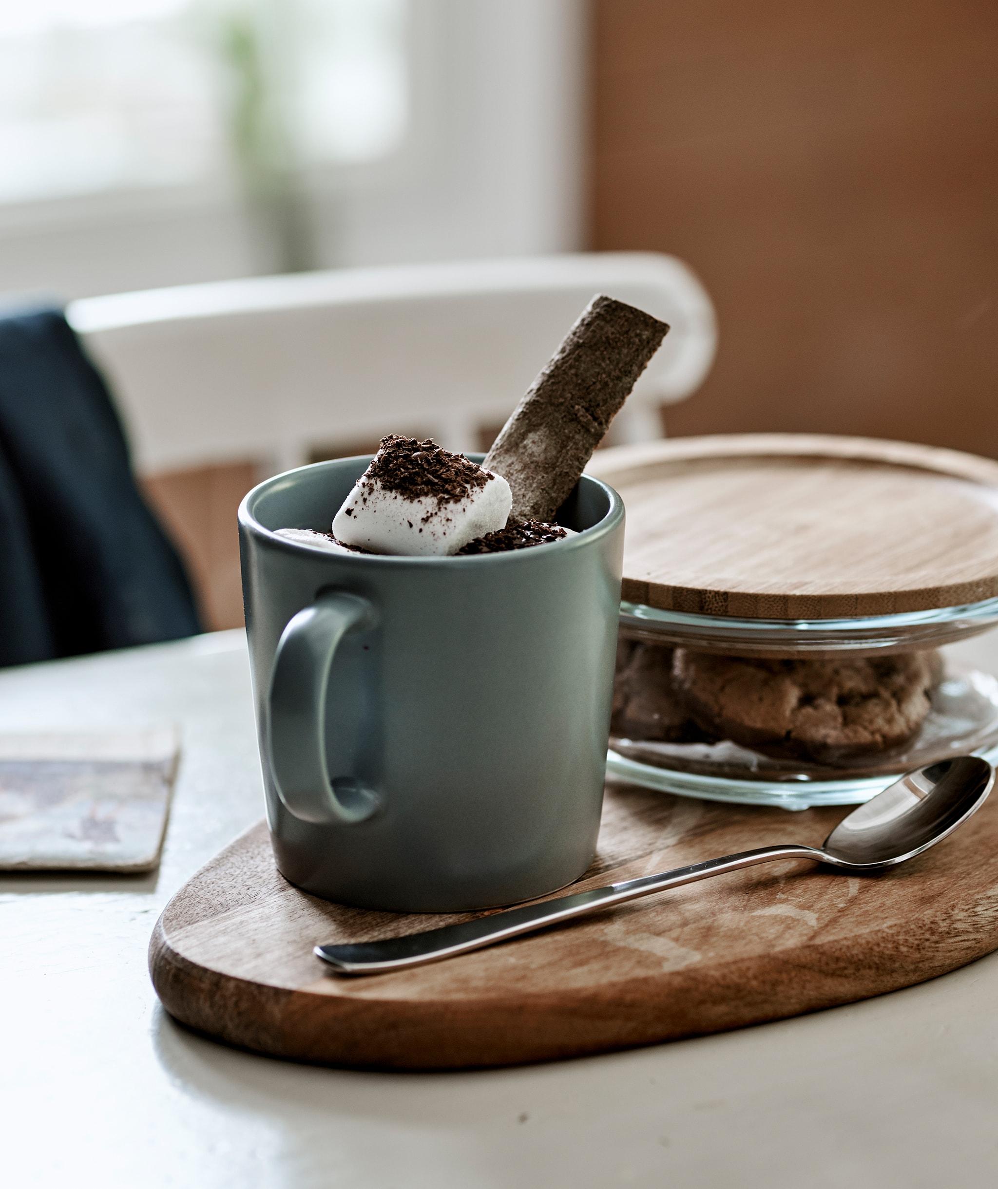 Minuman cokelat panas dengan marshmallow dalam cangkir berwarna abu-abu biru yang disajikan di atas talenan lengkap dengan kue dalam stoples kaca dengan penutup dari bambu.