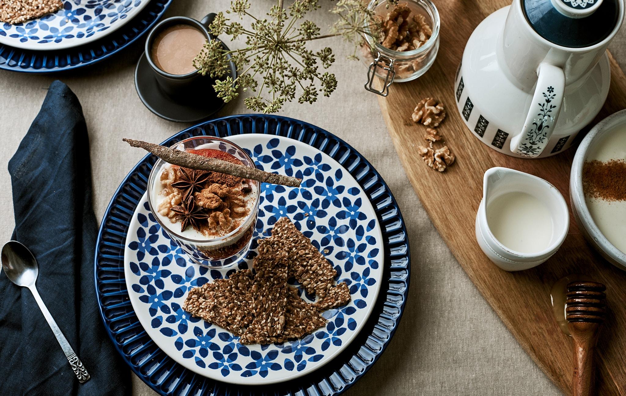 Meja makan untuk sarapan dihias menggunakan kain linen, piring biru bermotif, granola dalam gelas dan aksesoris kopi di atas talenan.