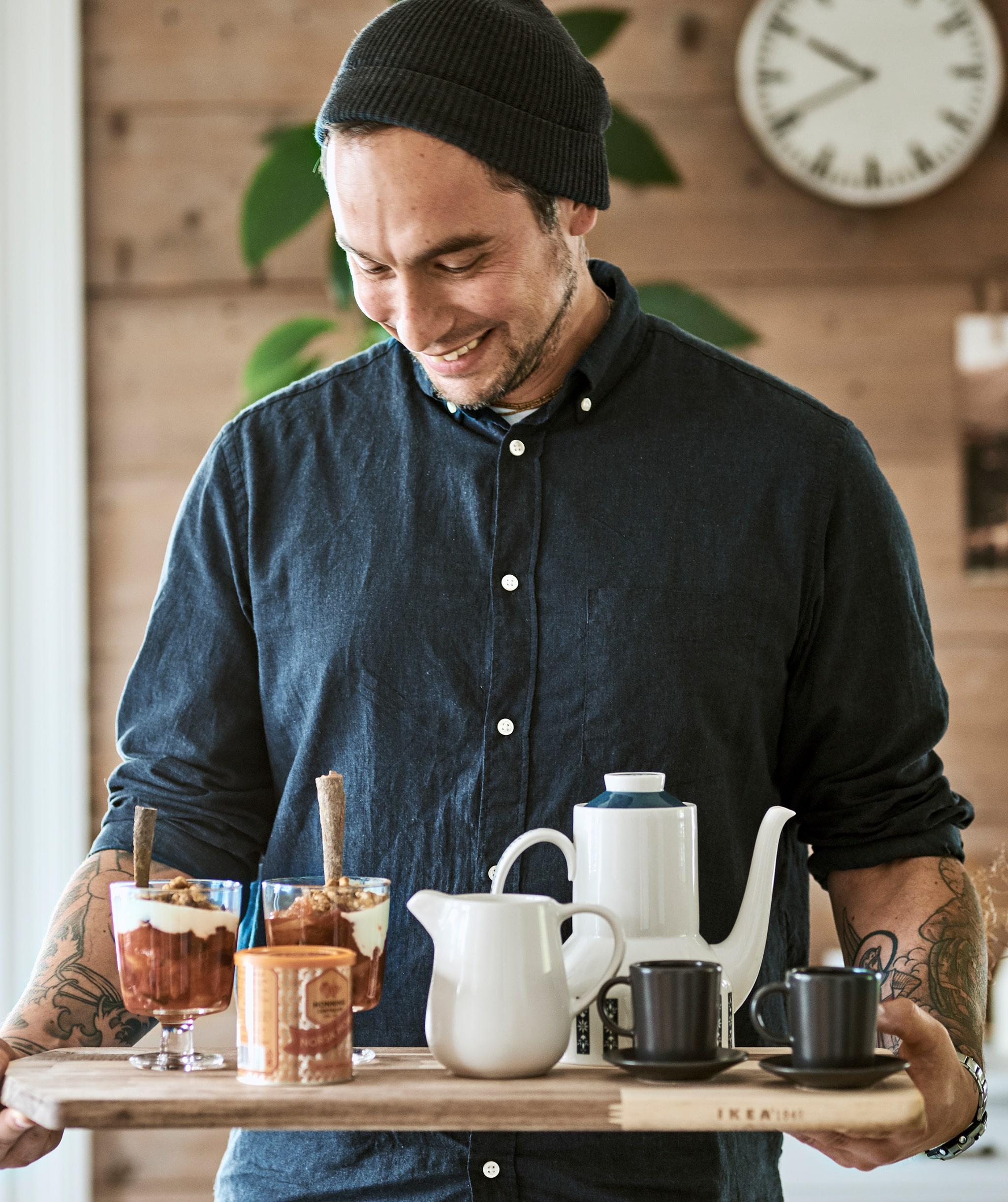 Seorang lelaki bertopi wol menggunakan talenan sebagai nampan untuk membawa teko kopi, cangkir espresso, dan granola dalam gelas.