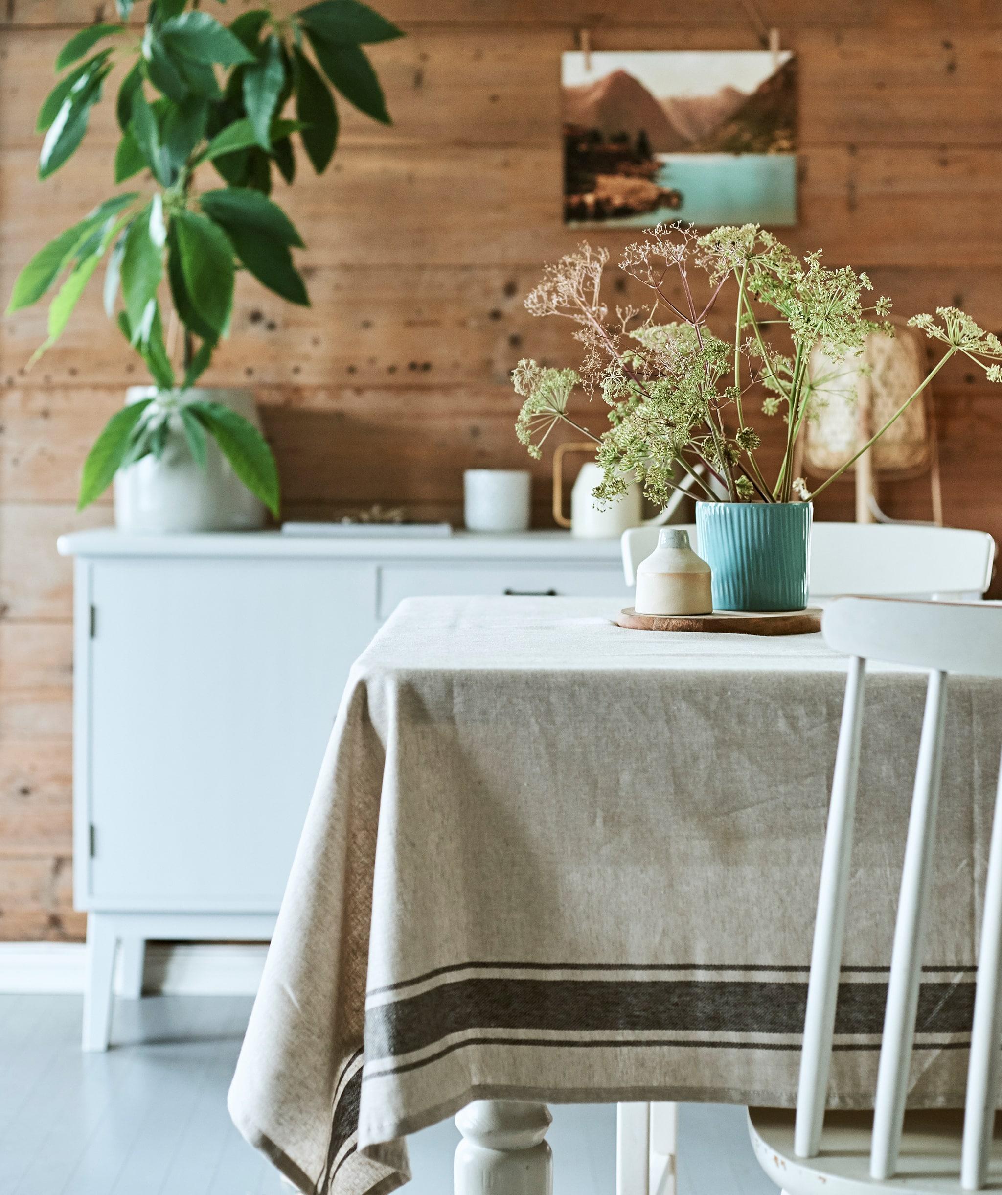 Ruang makan dengan gaya rustic yang berisi meja kayu yang ditutupi kain linen dan bunga-bunga liar dalam pot tanaman bergerigi berwarna biru yang diletakkan di tengah meja.