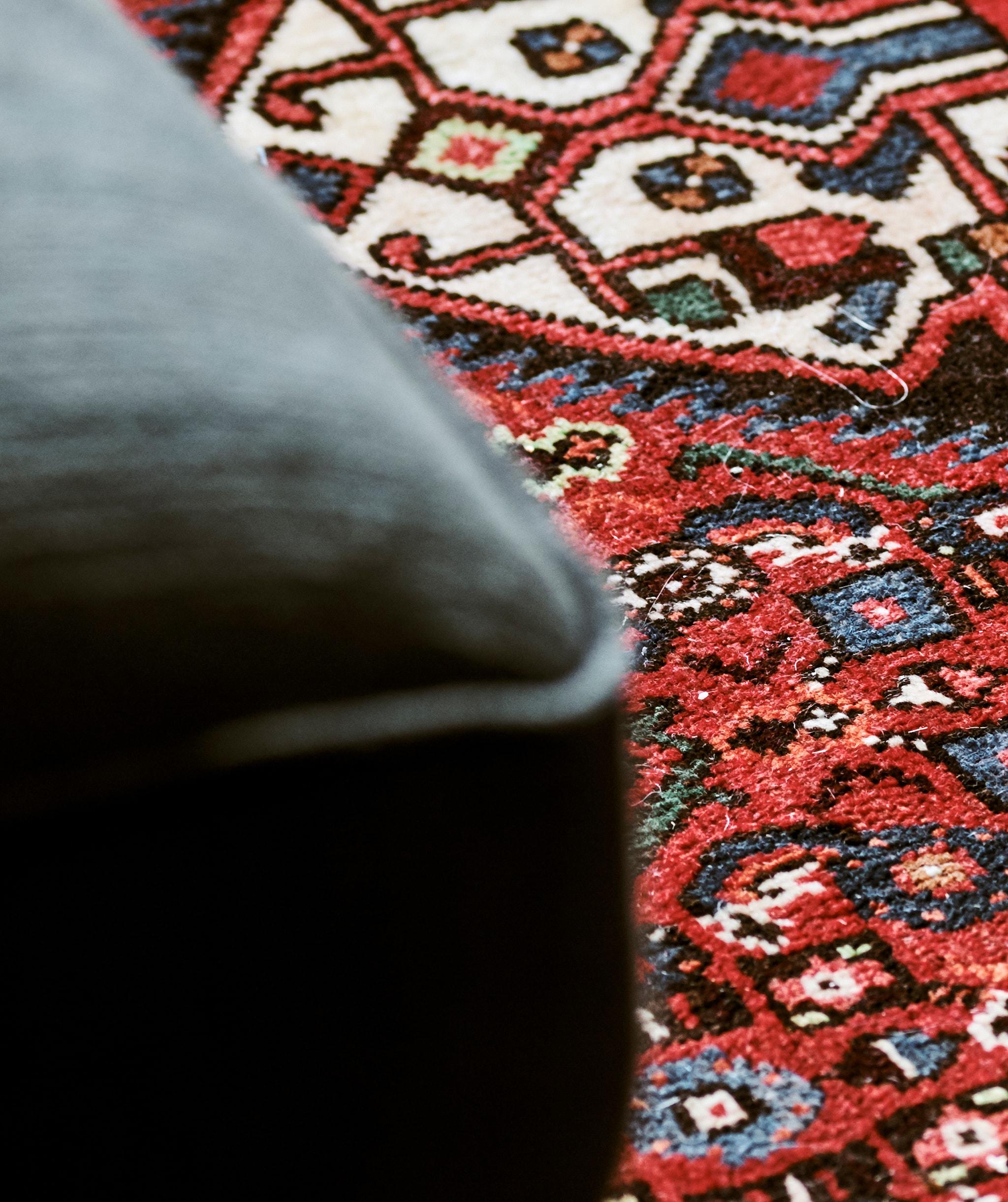Detail karpet Persia yang ditenun menjadi pola dengan bentuk biru dan hijau dengan latar belakang merah.