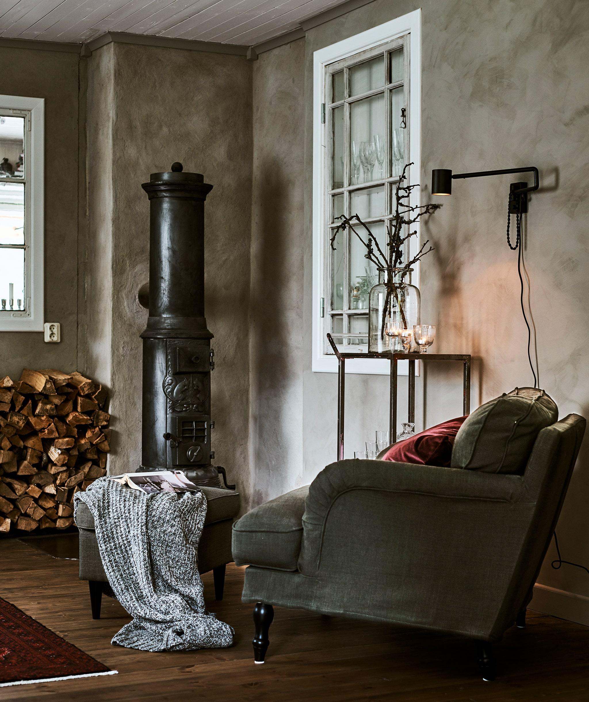 Sudut ruangan berdinding abu-abu dengan kursi berlengan berwarna hijau, bantal merah dan bangku kaki di samping tungku pembakaran kayu dan tumpukan kayu.