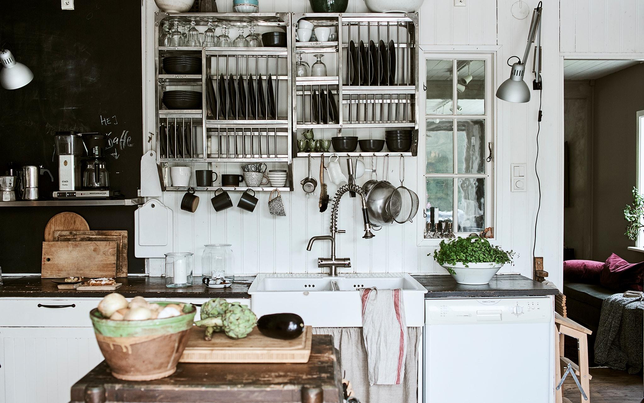 Dinding dapur dengan panel kayu putih dan cat papan tulis, ditambah rak terbuka bergaya industrial yang penuh barang pecah belah.