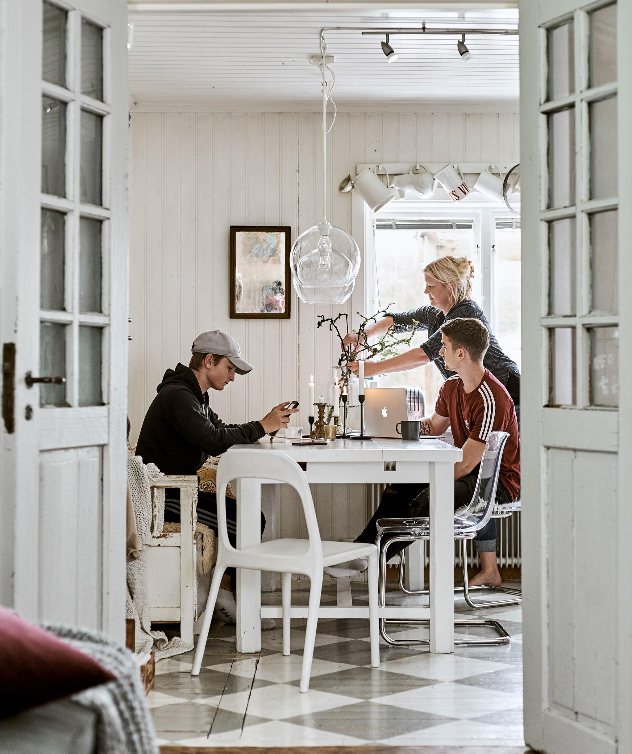 Pintu dengan kaca besar terbuka ke ruang makan dengan lantai kotak-kotak. Sebuah keluarga duduk di meja makan putih, lampu kaca menggantung di atasnya