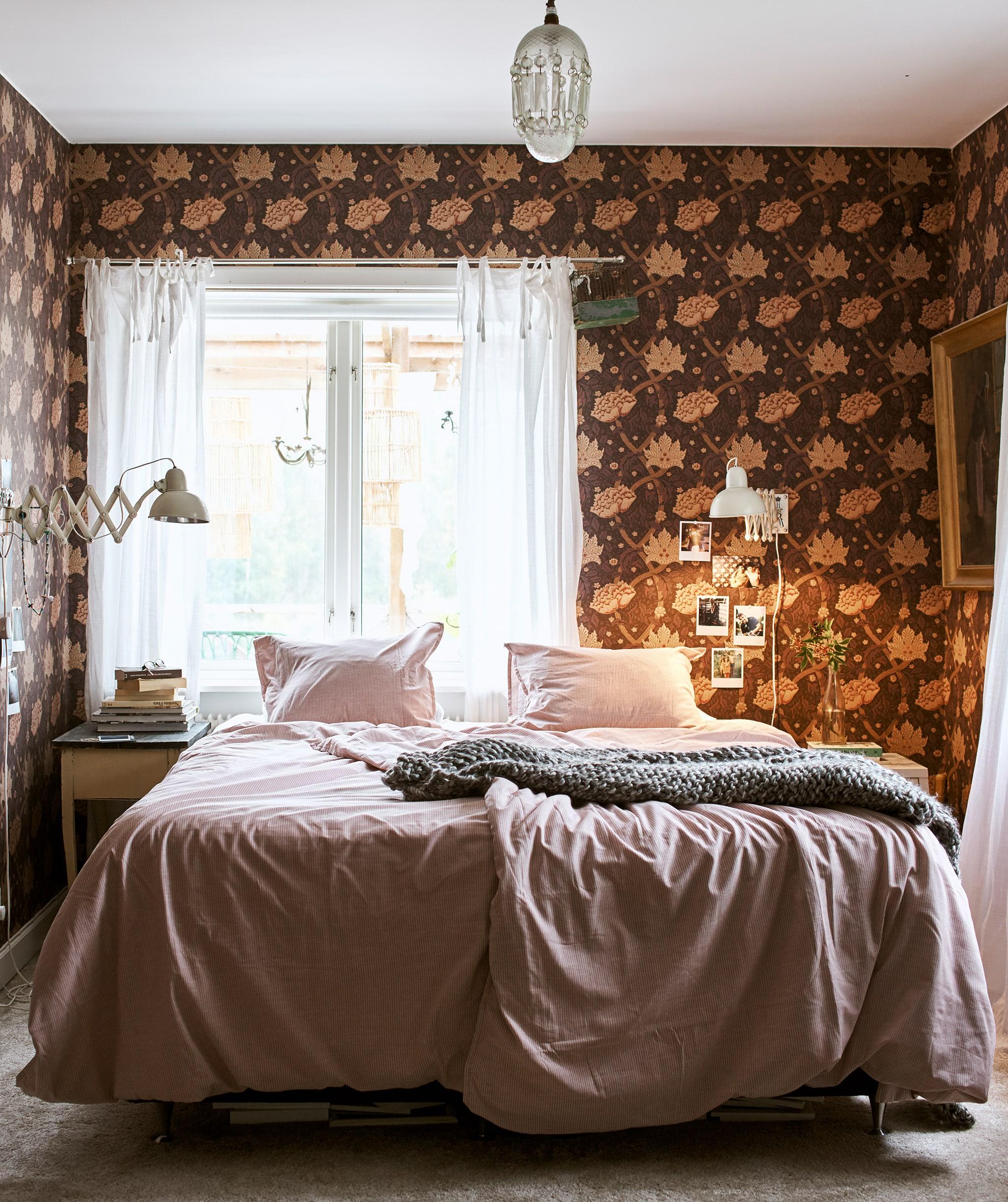 Tempat tidur dengan seprei merah muda dan selimut kecil abu-abu di tengah ruangan dengan lampu gantung dan wallpaper bermotif bunga.