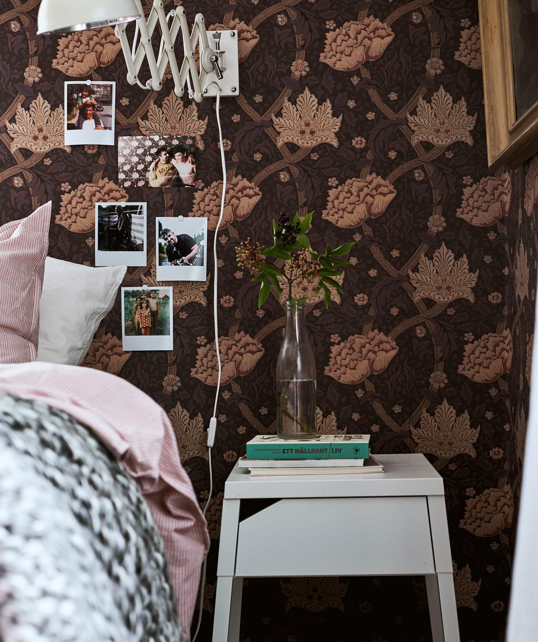 Tempat tidur dengan seprai merah muda di sebelah meja samping tempat tidur berwarna putih dengan buku-buku dan sebuah batang di dalam vas, foto-foto polaroids terpasang di dinding kertas.