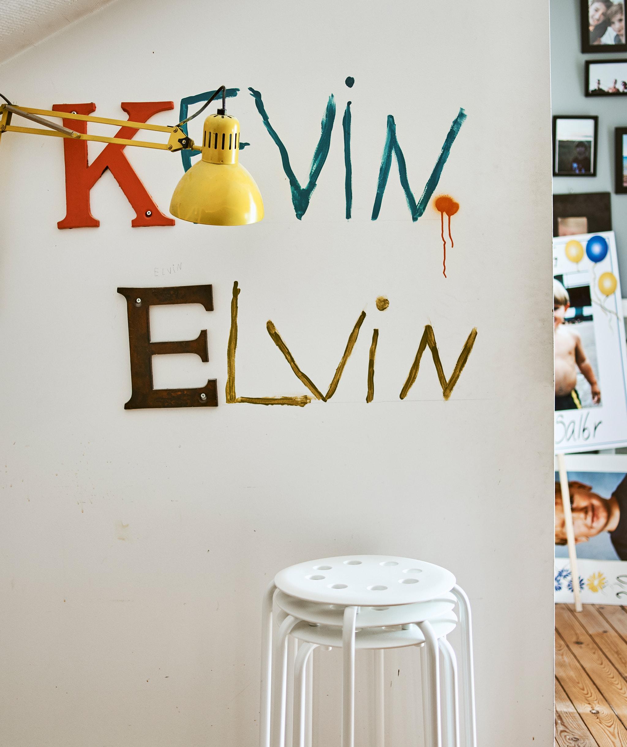 Bangku ditumpuk di sebelah dinding dengan nama Kevin dan Elvin yang dicat di atasnya dan lampu dinding berwarna kuning.
