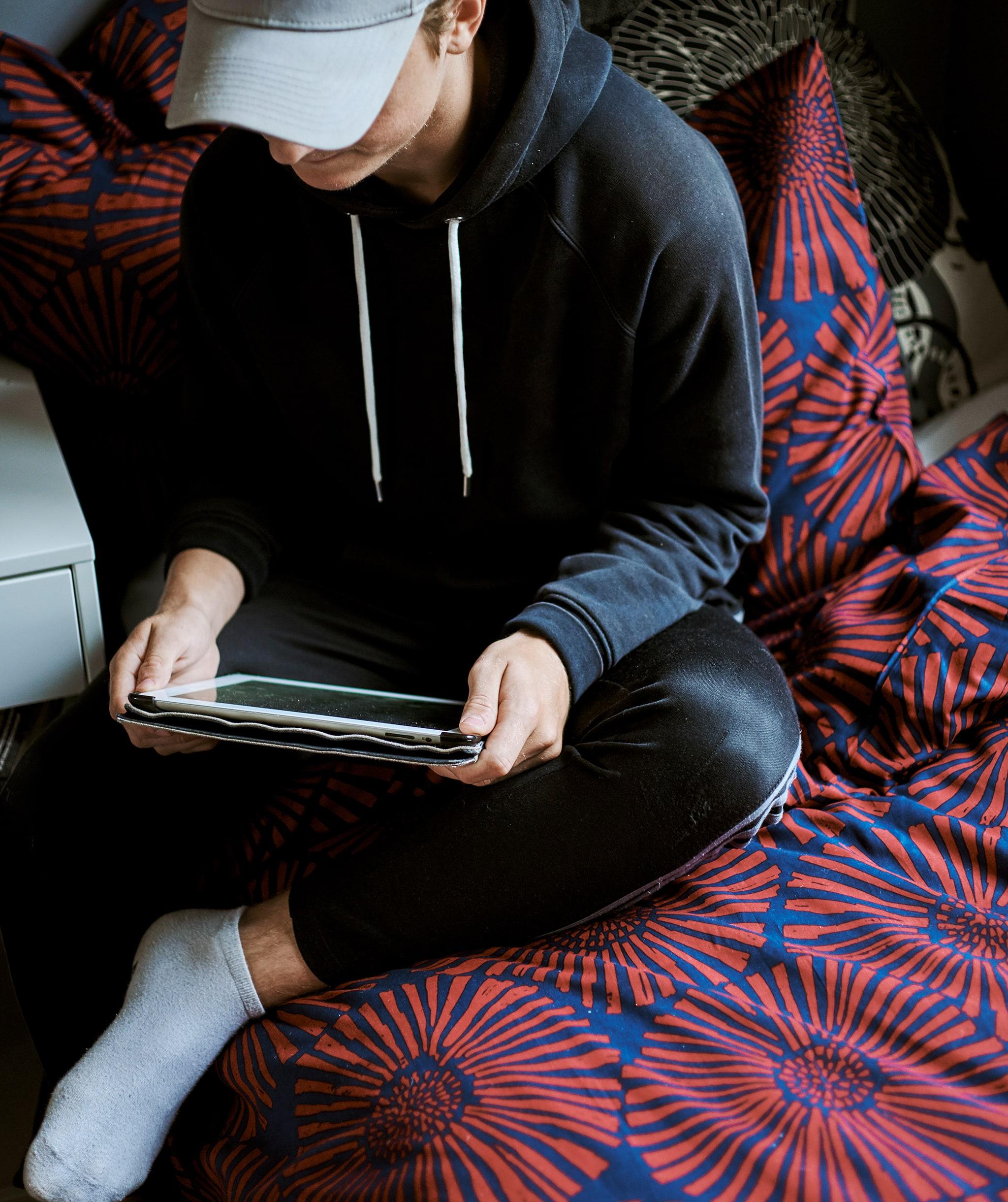 Seorang anak laki-laki mengenakan topi baseball, bermain tablet duduk di tempat tidur dengan selimut bergambar grafik print berwarna merah dan biru.
