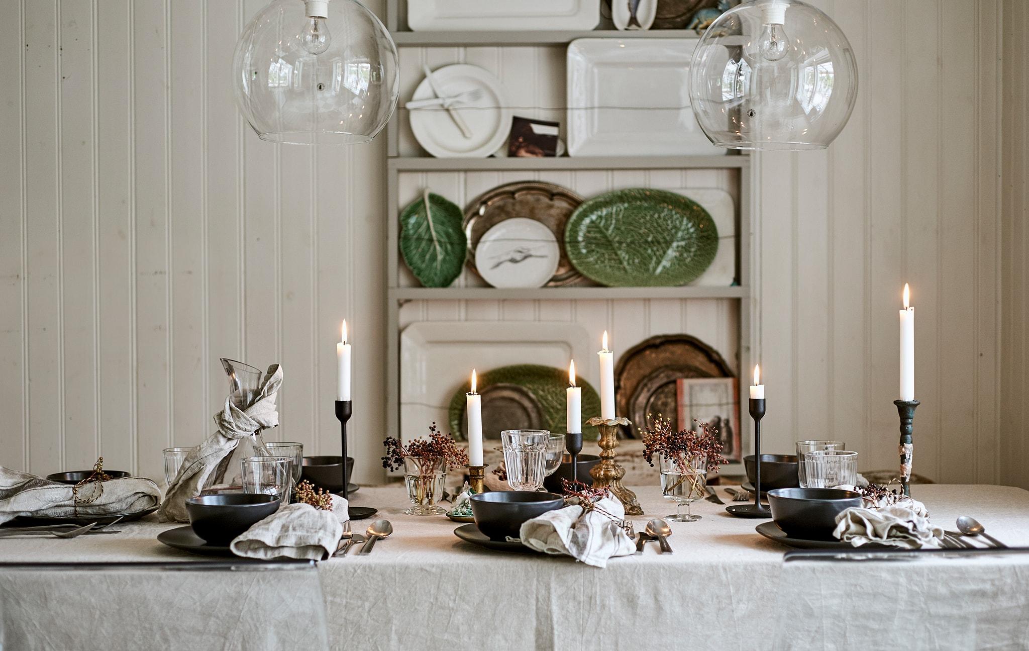 Meja makan yang ditata meriah dengan taplak meja linen, lilin, gelas-gelas kaca dan penataan tempat duduk dengan serbet yang dihias.