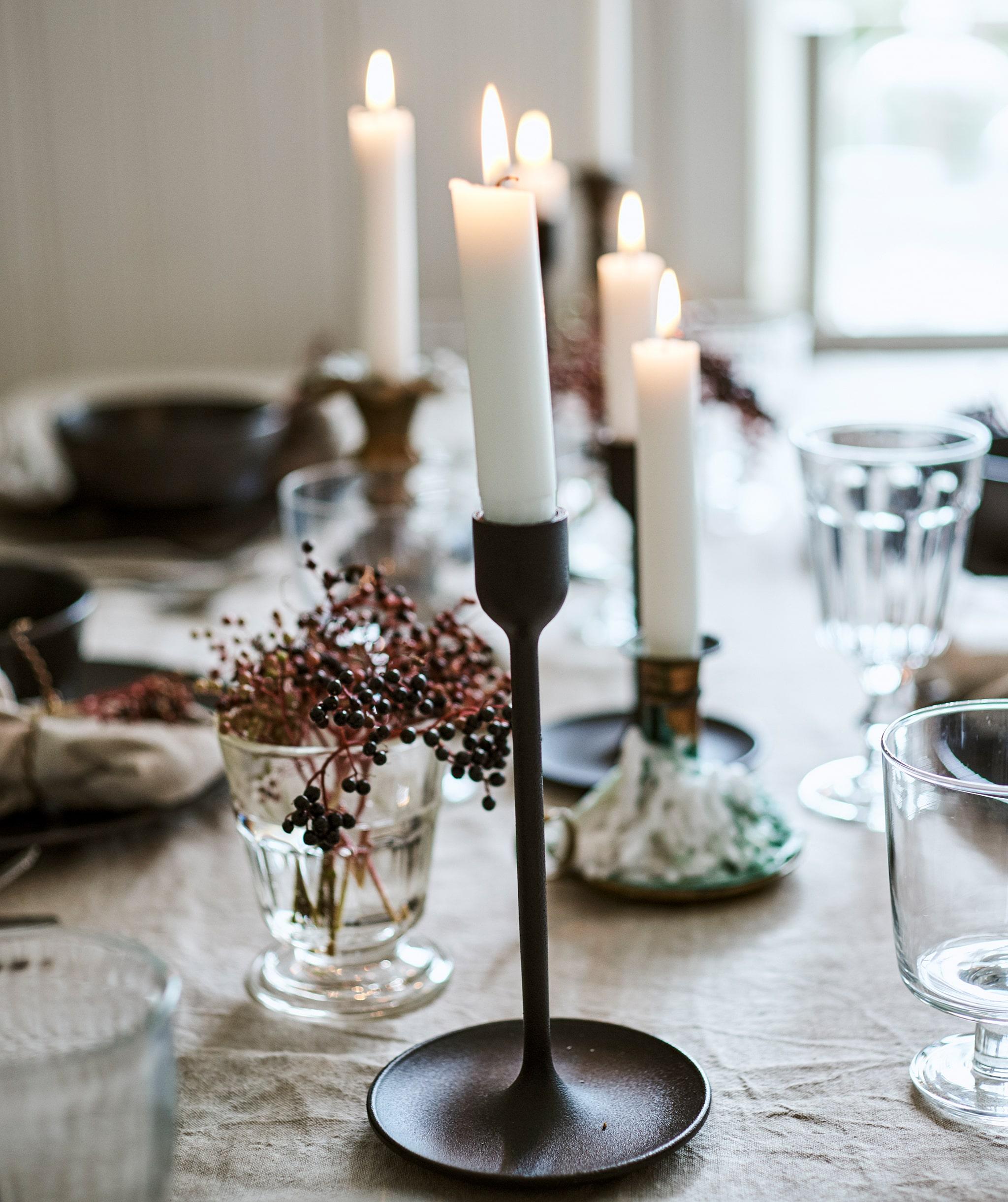 Menyalakan lilin dalam gabungan tempat lilin berwarna hitam dan kuningan dengan penataan meja lengkap dengan taplak meja linen, gelas-gelas dan buah berry dalam vas.