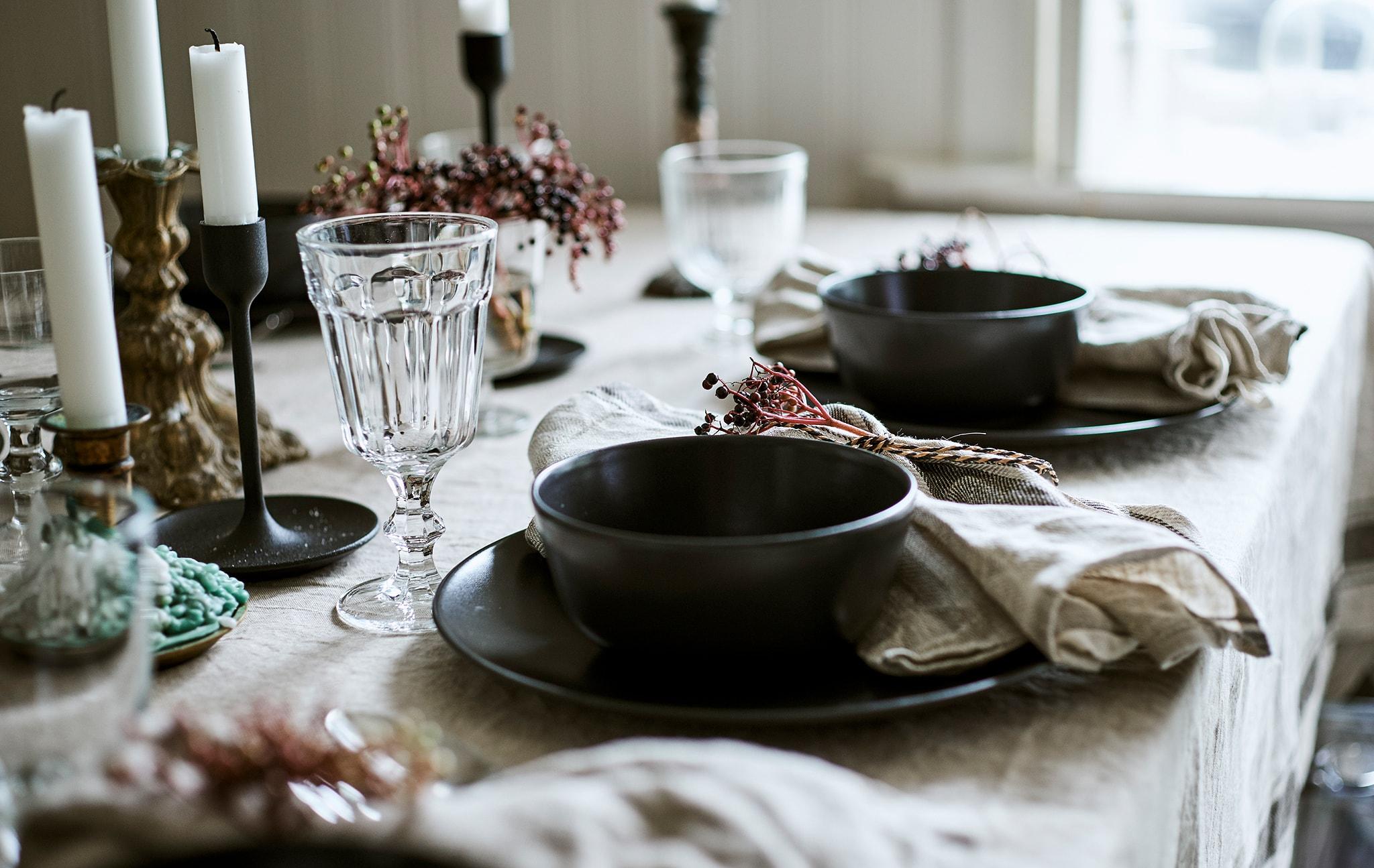 Dua penataan di atas meja yang ditutupi linen, masing-masing memiliki mangkuk abu-abu biru yang diletakkan di atas piring dengan gelas kaca dan serbet yang diikat.