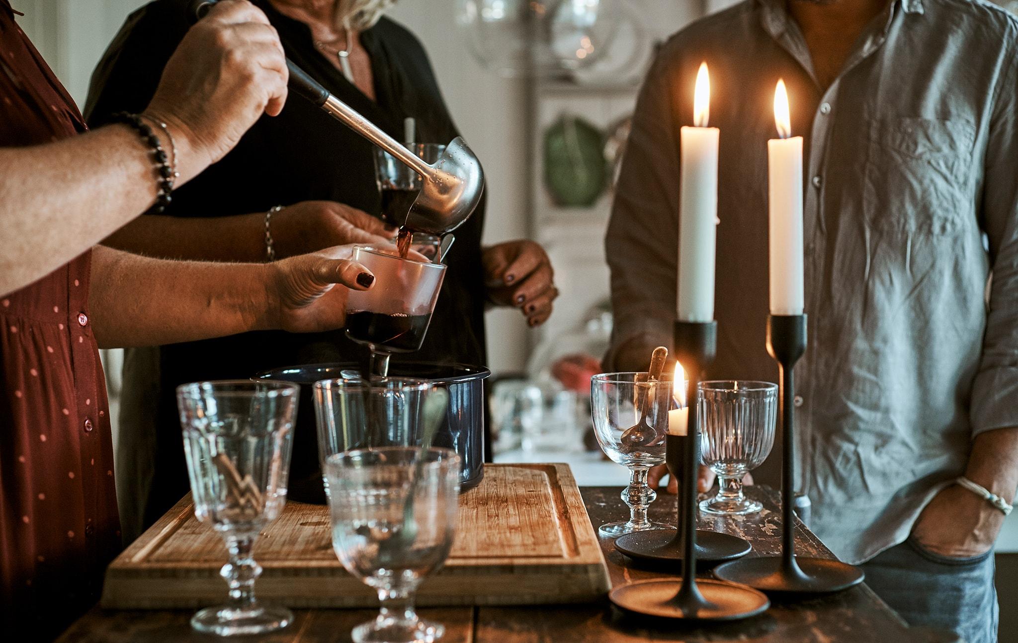 Orang-orang berdiri di meja tengah dapur dengan gelas-gelas dan lilin-lilin yang menyala dan sepanci minuman panas, seseorang menyendok minuman ke gelas.