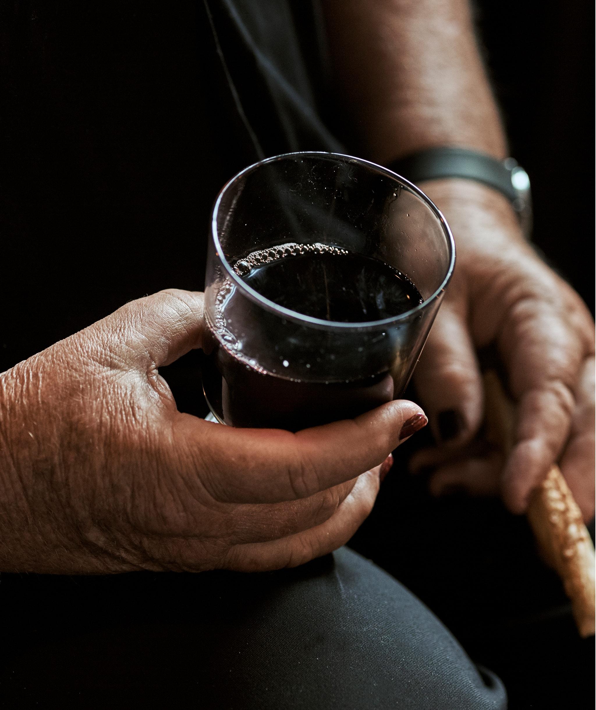 Seorang wanita dengan kuku dicat duduk dan memegang segelas anggur di satu tangan dan roti di tangan lainnya.