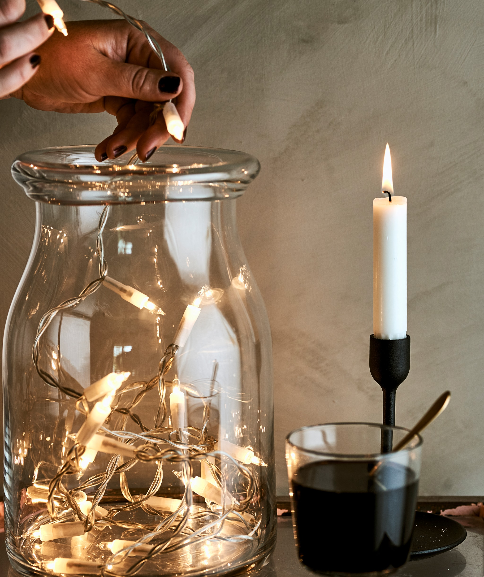 Seorang wanita mengisi stoples kaca dengan lampu dekoratif di sebelah segelas minuman anggur dan menyalakan lilin dalam tempat lilin berwarna hitam.