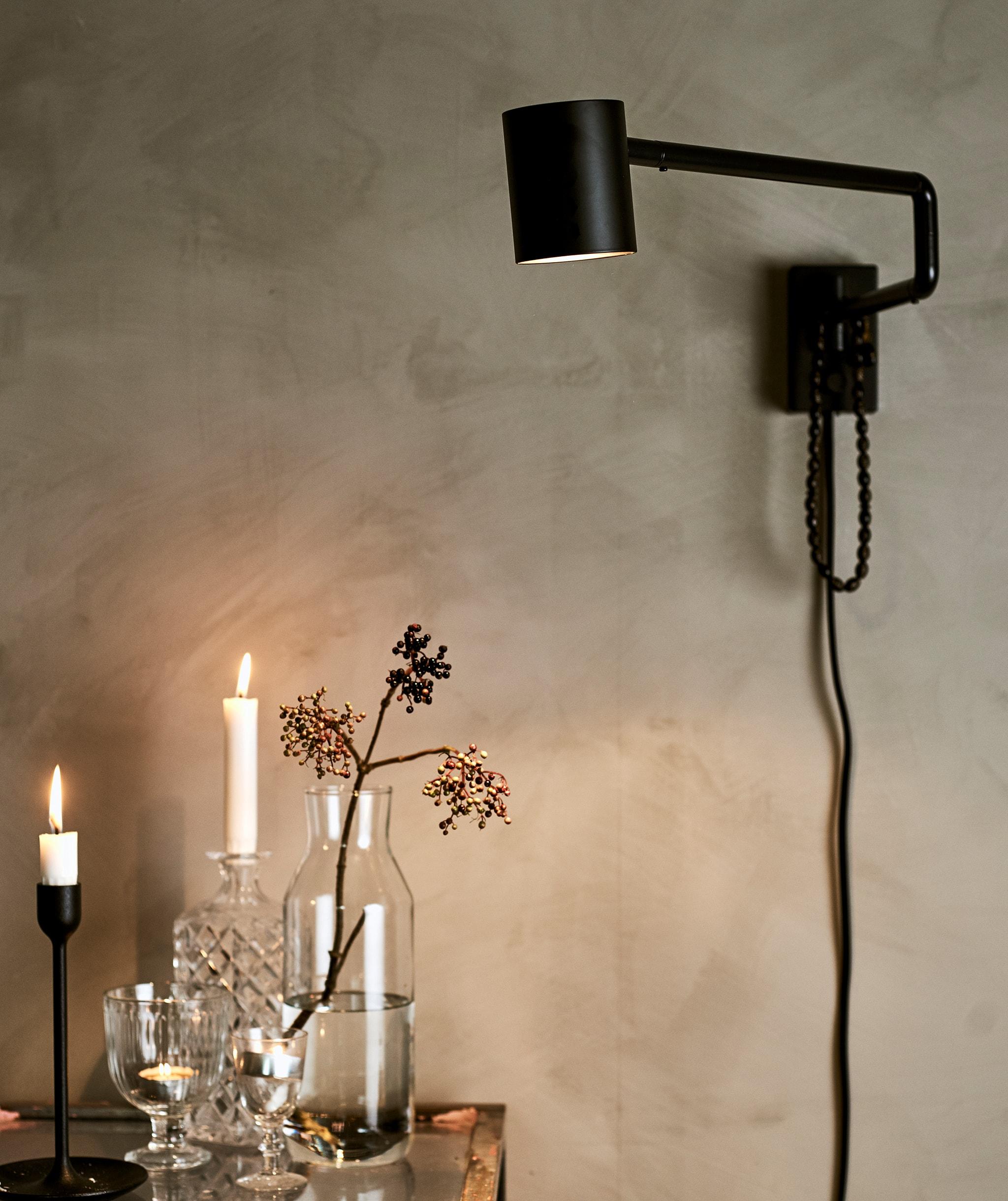 Lampu dinding berwarna hitam di dinding yang dicat abu-abu, menyinari lampu di meja kaca yang berisi gabungan bermacam gelas, lilin, dan tempat lilin.