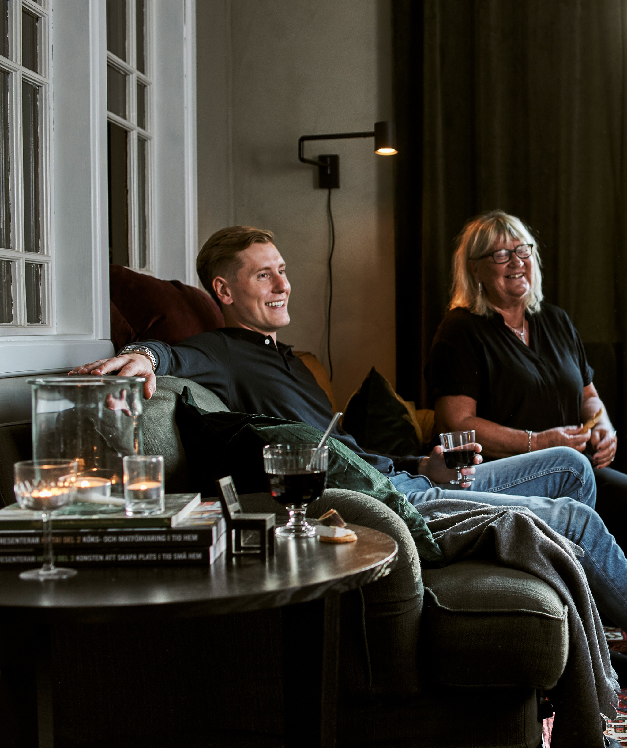 Seorang pria dan wanita duduk di sofa hijau dengan bantal dan selimut kecil, minuman dalam gelas, tempat lilin dan buku-buku ada di atas meja tamu.