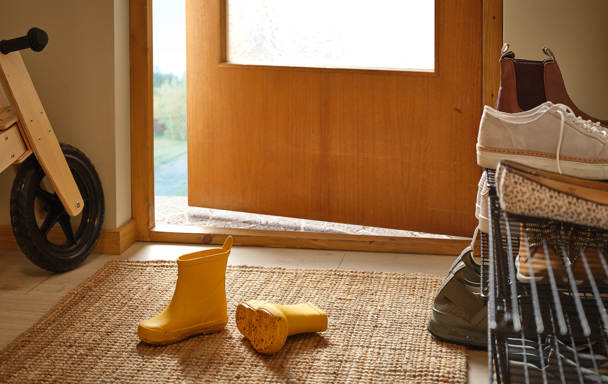 Hallway with a pair of children's wellingtons on the rug, filled shoe rack on the side, a wooden kid's bike against the wall.