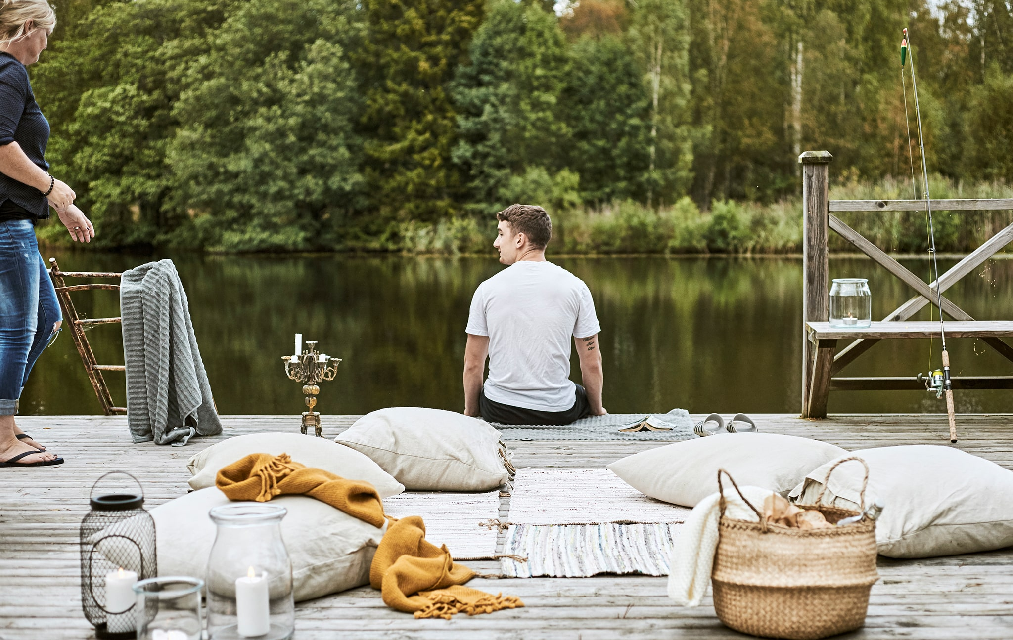 A boy sits on the edge of a jetty next to a woman in flip-flops. On the deck are rugs, cushions, throws and a picnic basket.