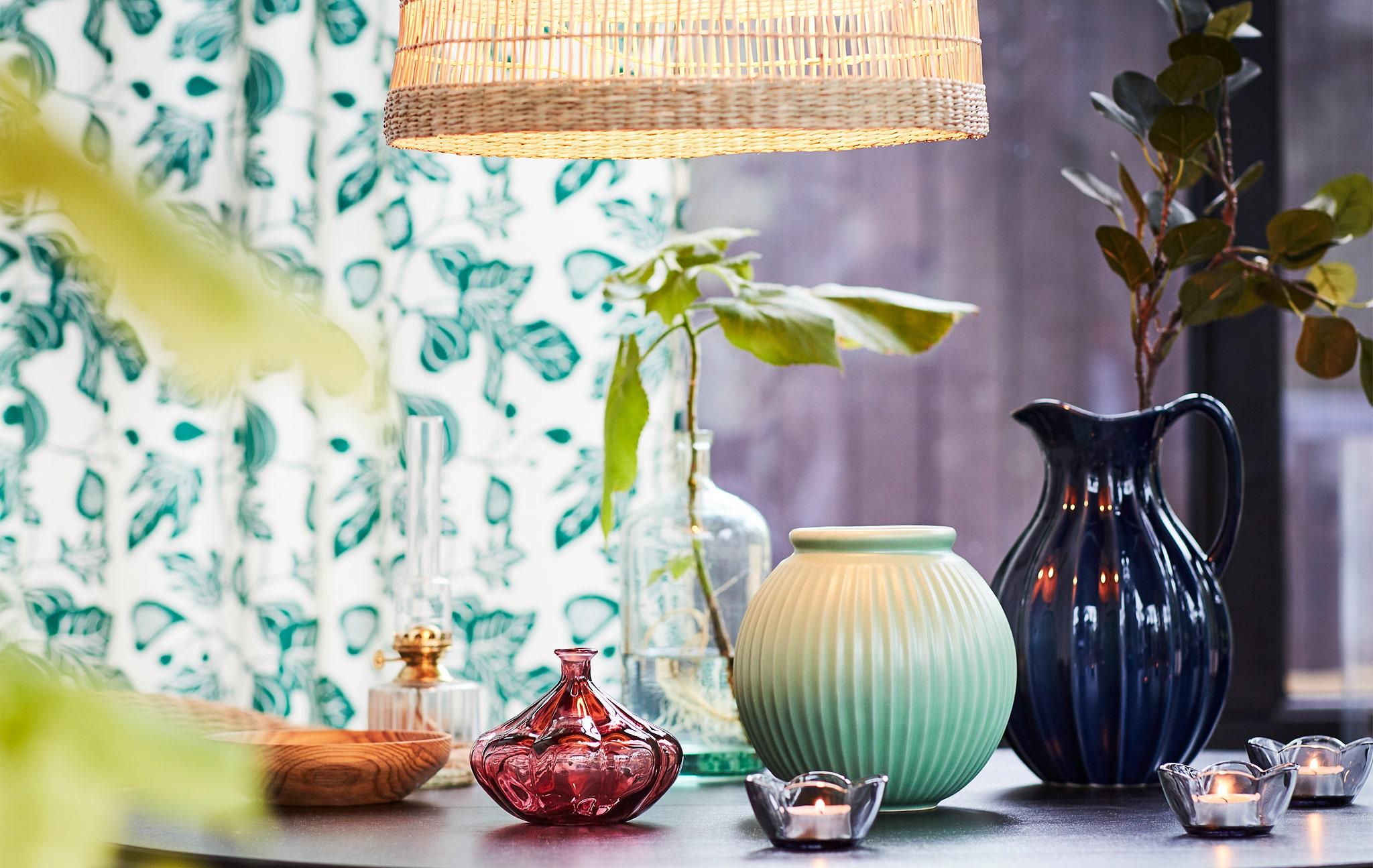 Sebuah meja yang dihiasi dengan vas kecil dan lilin dengan sedikit daun hijau dan penanda musim semi.