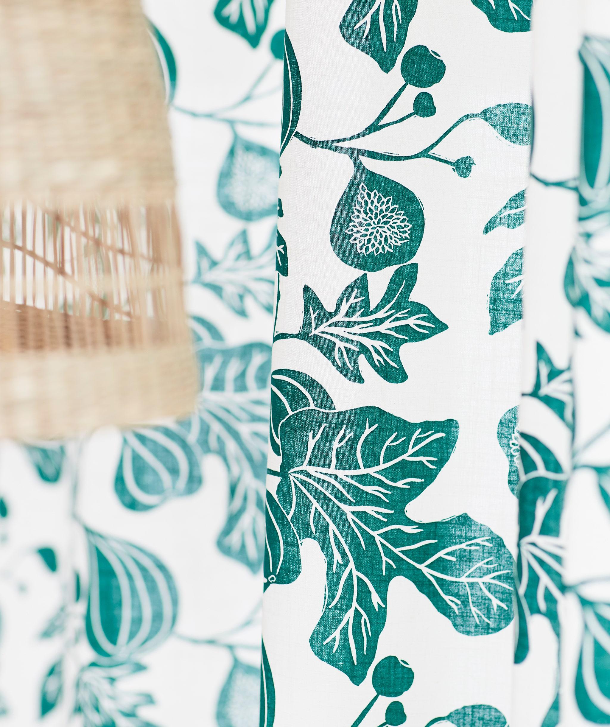 Tirai putih dengan pola ranting pohon ara warna hijau, berada di sebelah lampu plafon yang terbuat dari serat pisang alami.