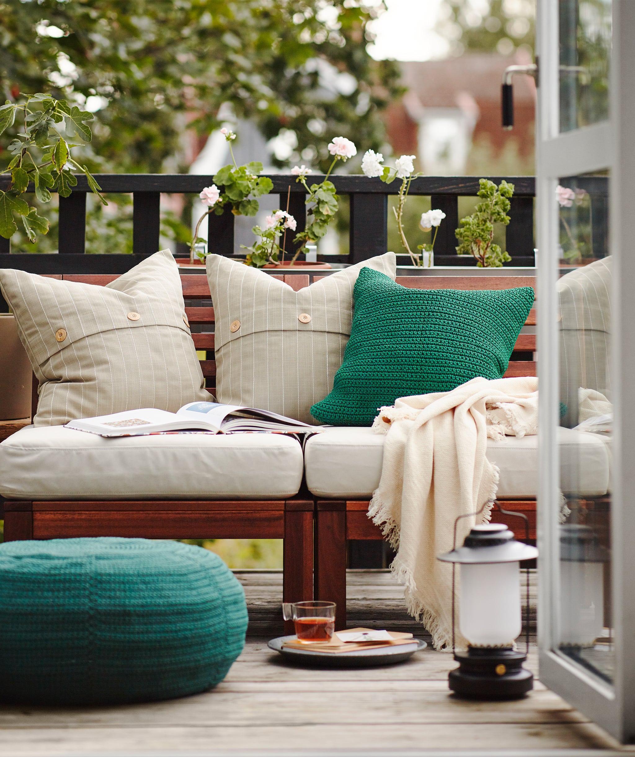 Sarapan di balkon dengan pintu terbuka dan banyak bantal, selimut, dan beberapa perabotan luar ruangan.