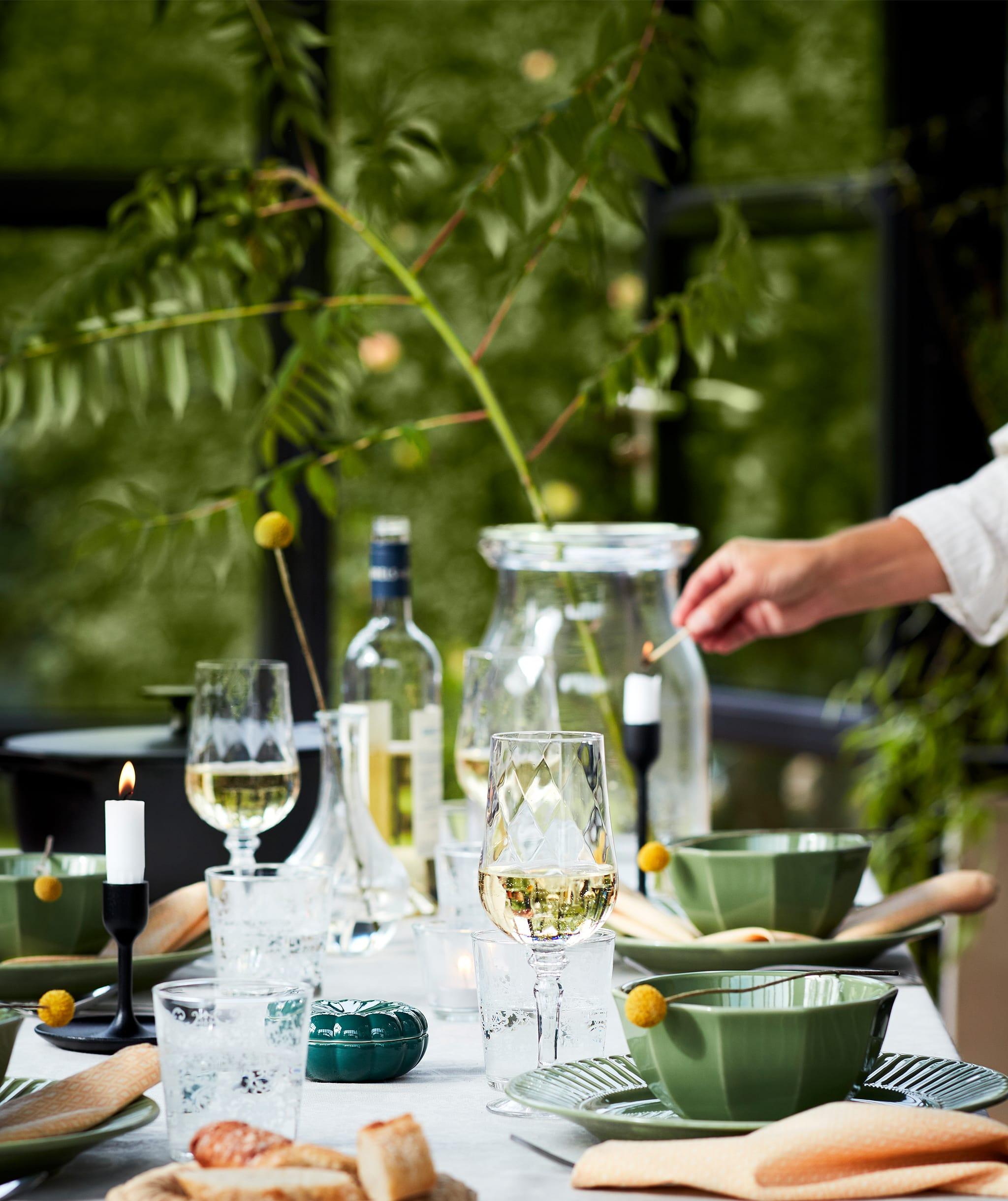 Meja yang ditata dengan baik untuk makan malam di luar ruangan dengan piring hijau, gelas anggur, lilin, dan banyak lagi. Tampil dengan suasana alam.