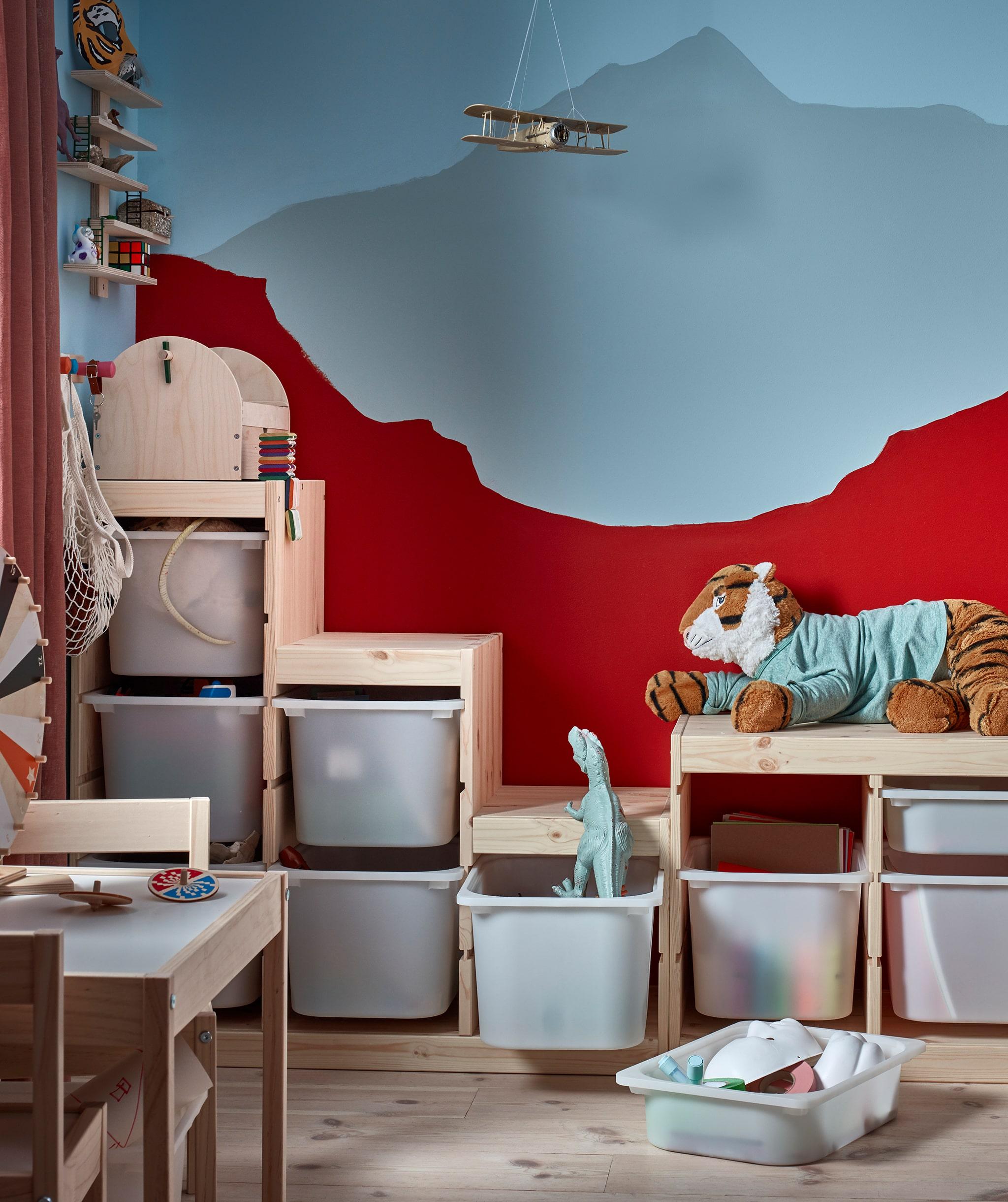 Sudut kamar anak di mana unit rak penuh mainan sengaja ditata tidak beraturan cocok dengan pewarnaan dinding di belakangnya.