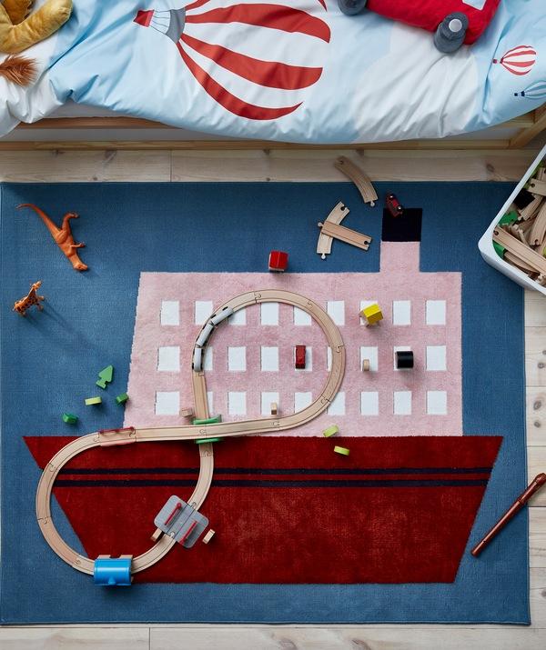Karpet dengan motif perahu, diletakkan di bawah tempat tidur anak, dengan kereta api kayu dan mainan lainnya yang berserakan.